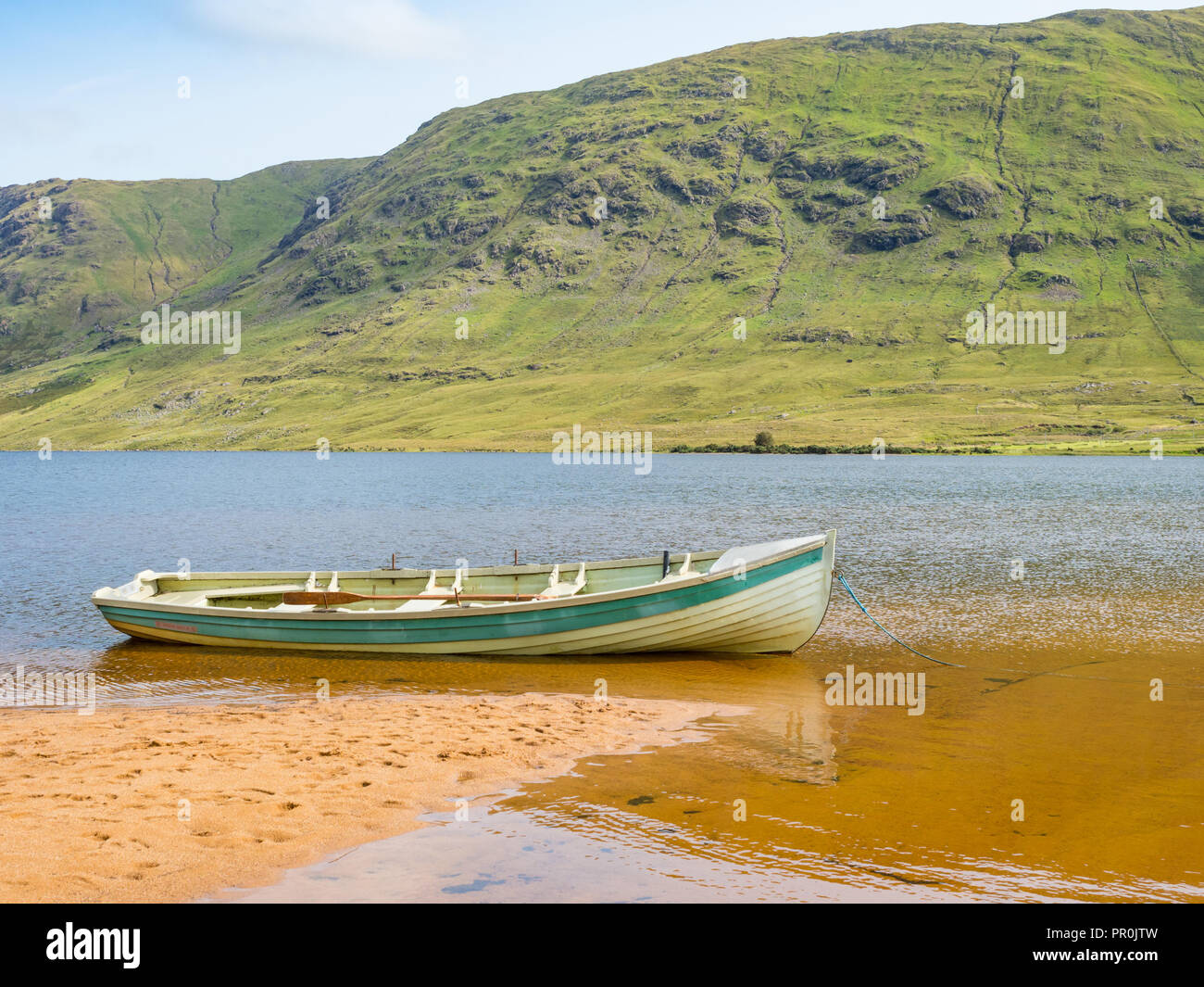 A boat on the beach at scenic Lake Nafooey in the Connemara region of County Galway in Ireland. Stock Photo