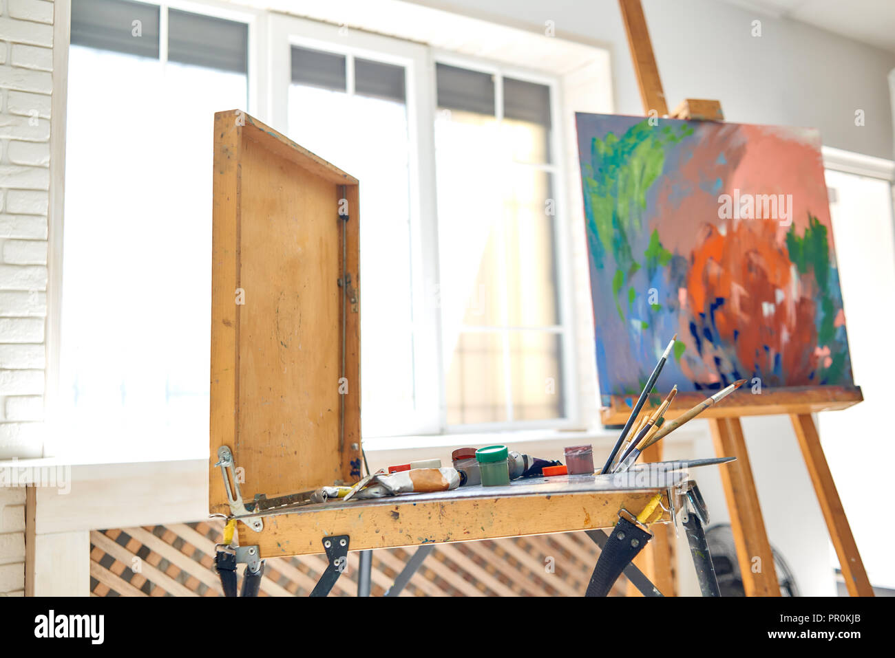 Close up of drawing instruments and tools, artist watercolors brushes and easel with abstract picture on background against big window at studio. Artist workspace in painter studio. Concept of hobby. - Stock Image