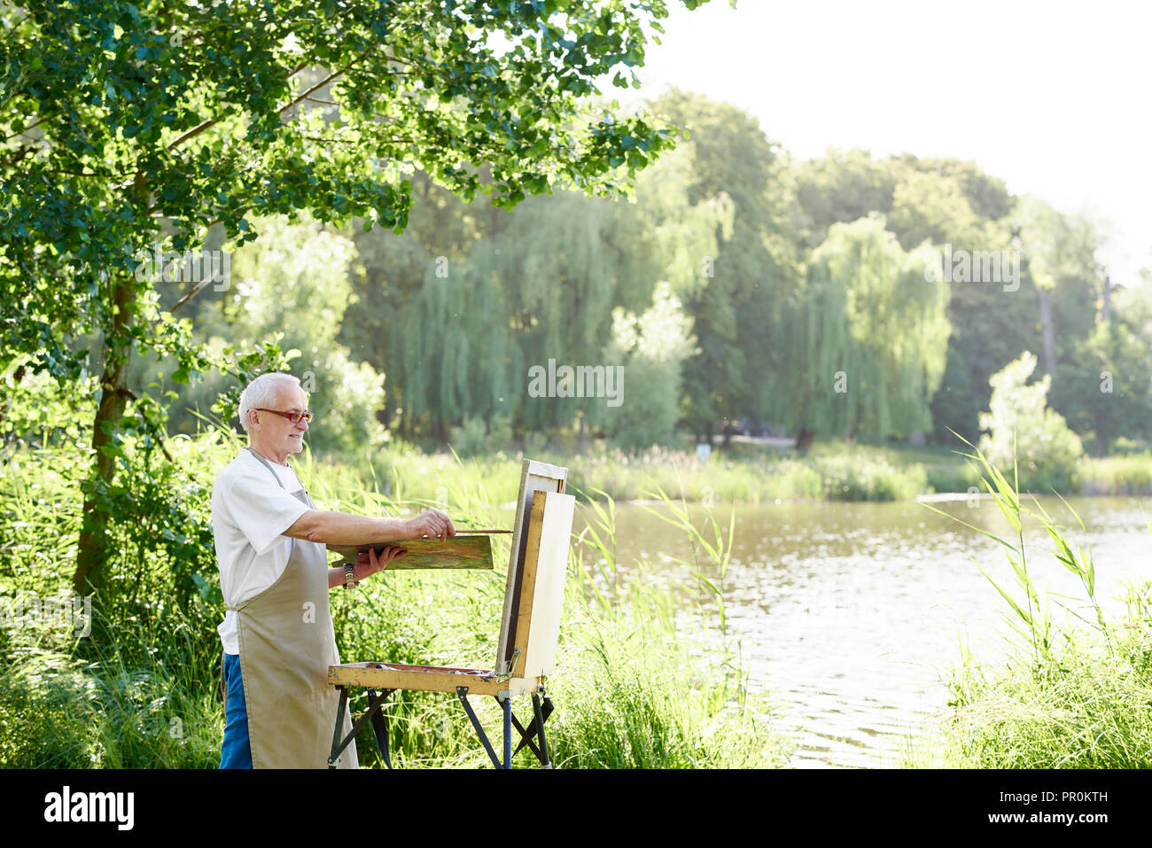 Serious male artist holding brush and painting picture on easel on open air. Senior painter, wearing in apron and modern glasses, using palette with paints working on his new masterpiece against lake. - Stock Image