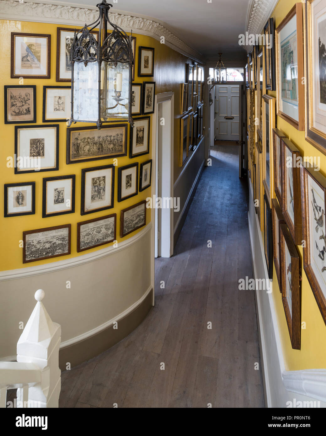 Curved picture wall in entrance hallway with vintage glass lantern - Stock Image