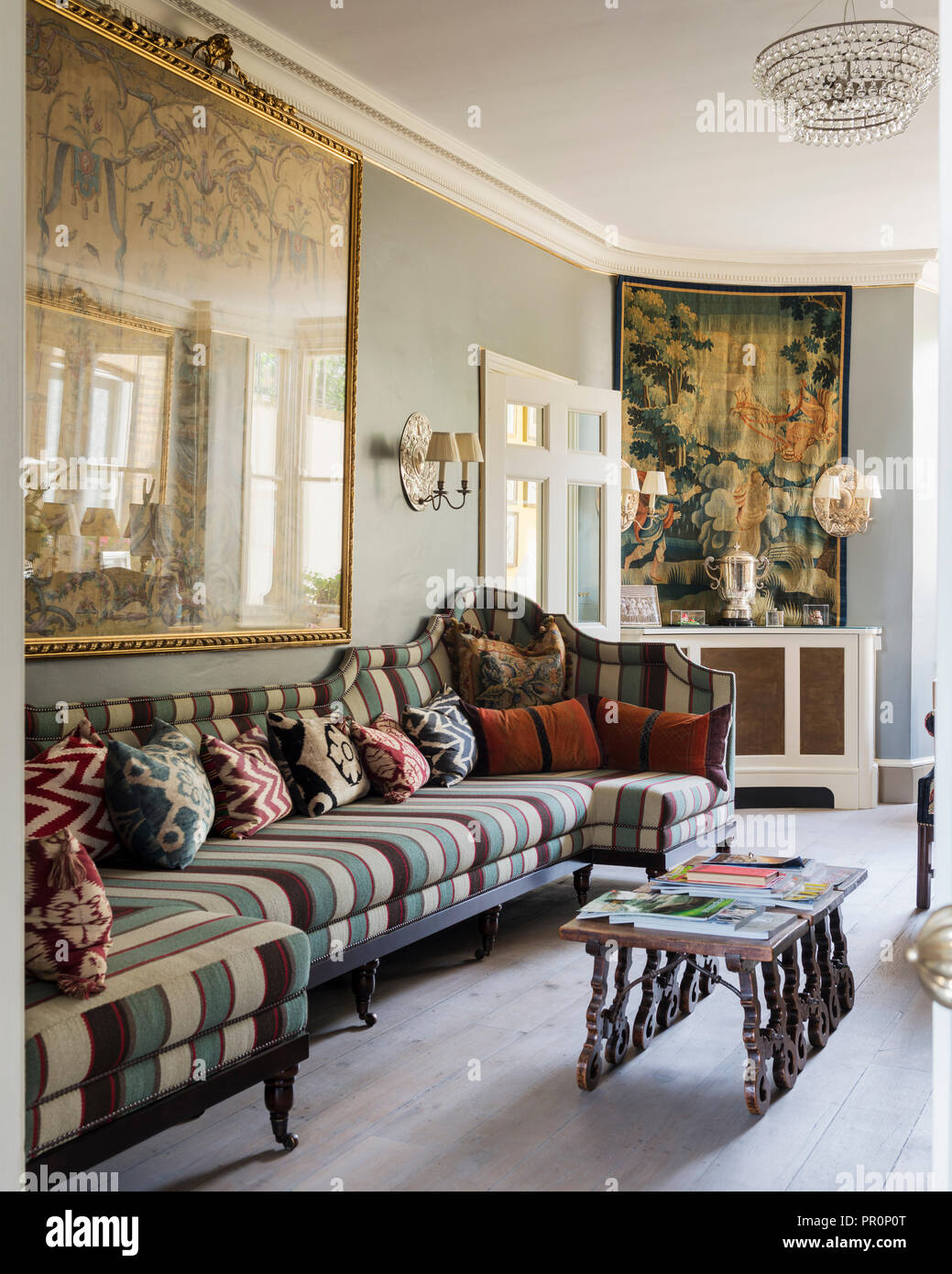 18th century French tapestry with banquette upholstered with Andrew Martin stripe - Stock Image