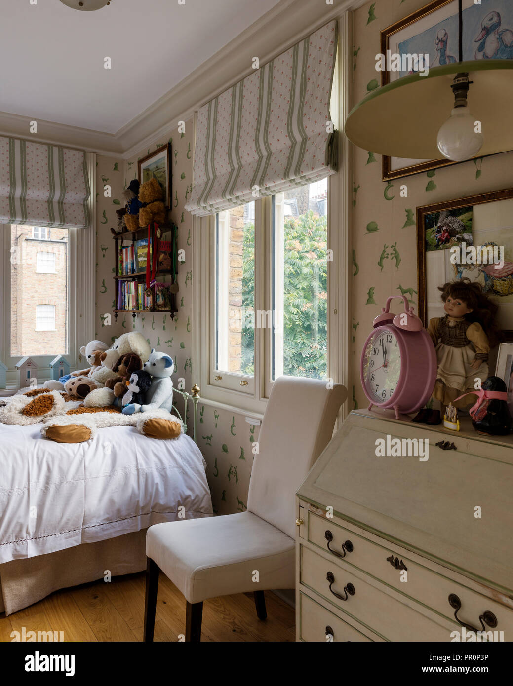 Soft toys on single bed in childs room Stock Photo