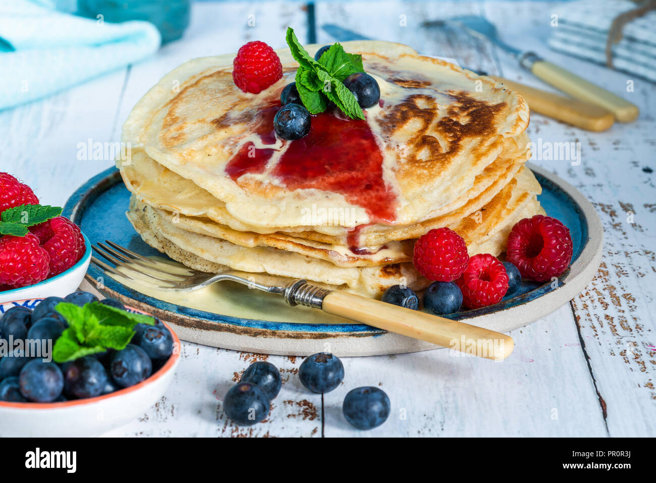 A stack of pancakes with fresh fruit, jam and cream on a plate - Stock Image