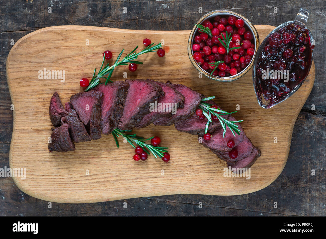 Sliced venison steak on wooden board with lingonberries - top view Stock Photo