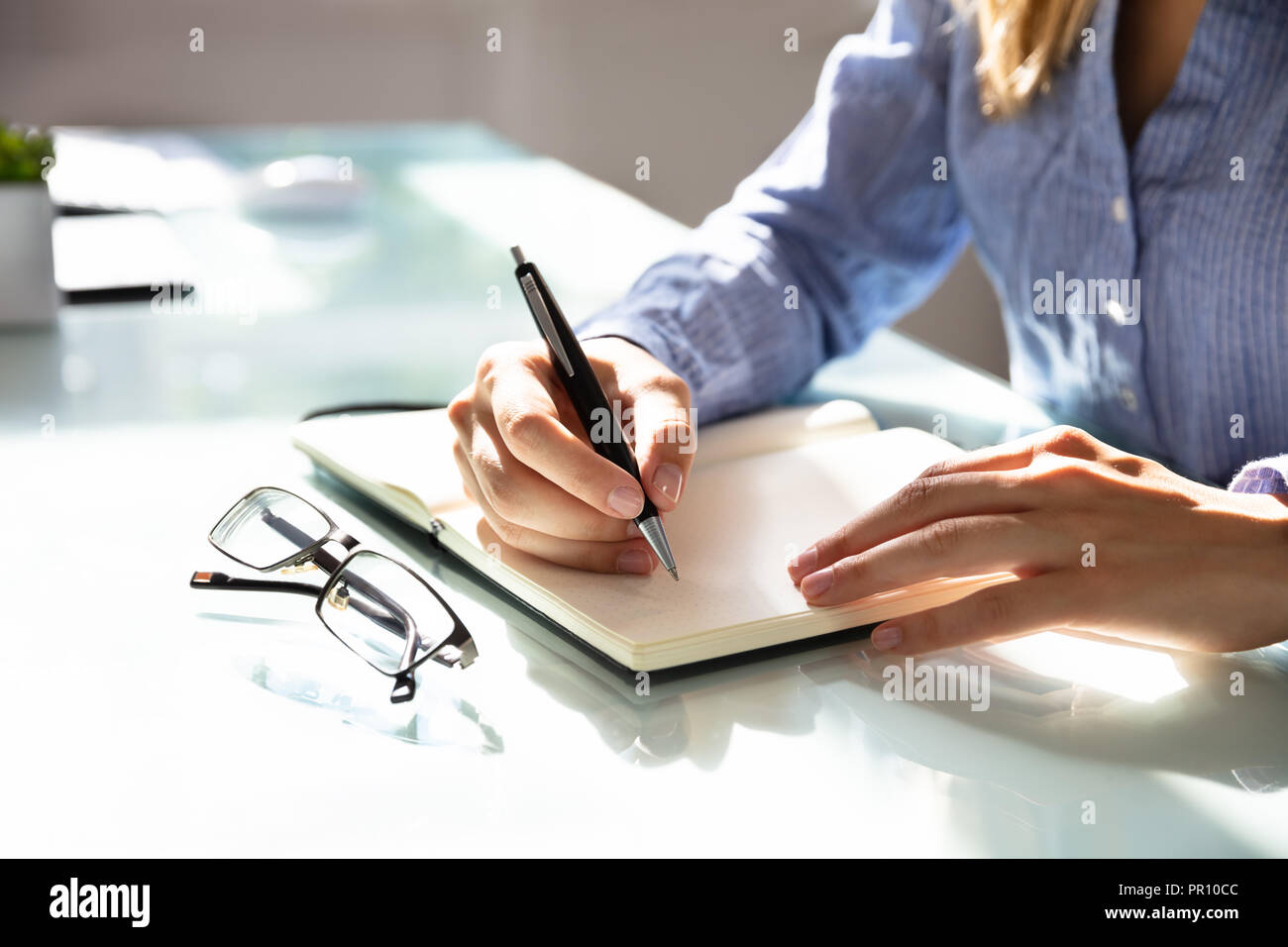 Close-up Of A Businesswoman's Hand Writing Notes In Notebook With Eyeglasses On Desk - Stock Image