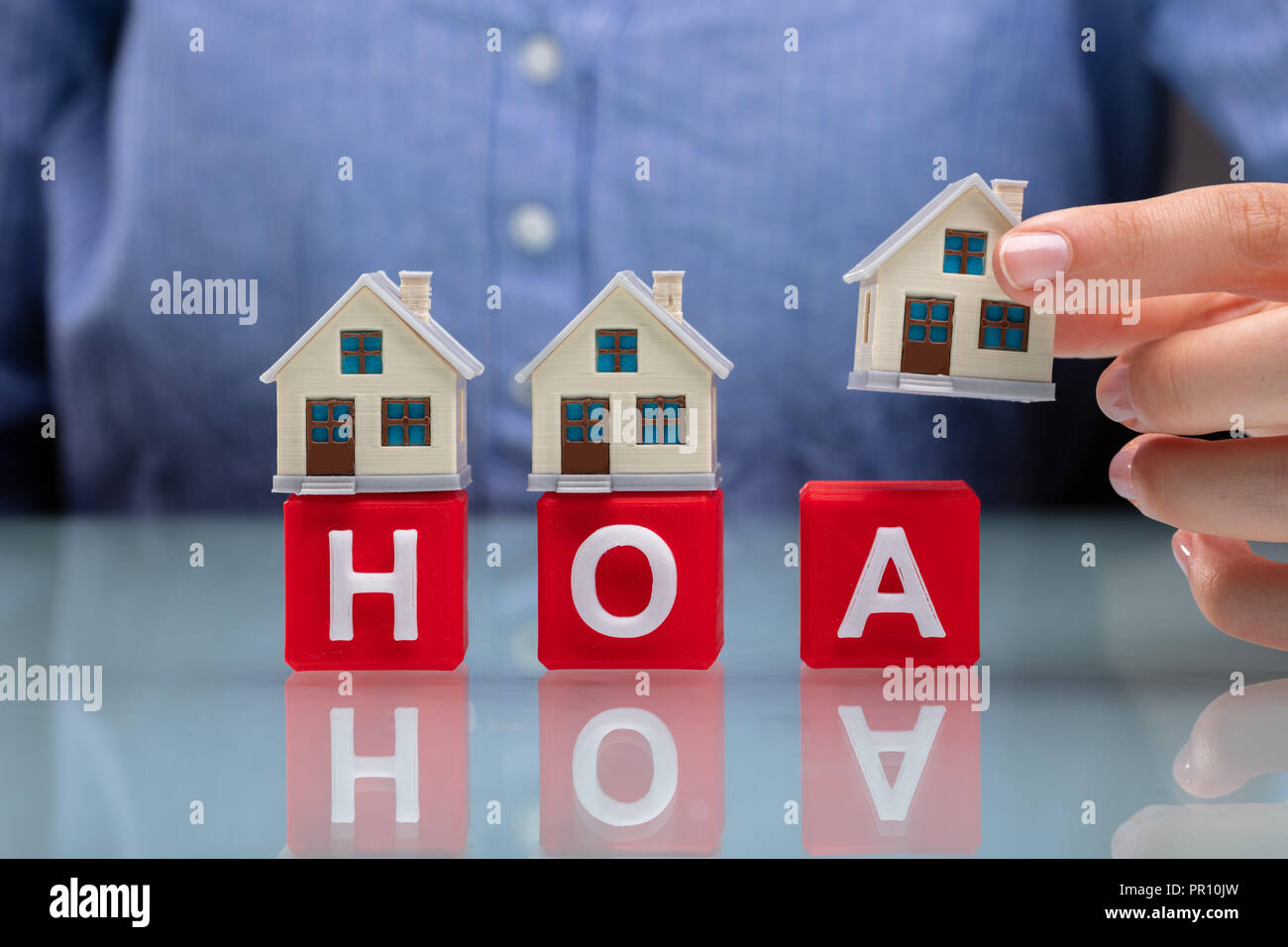 Businesswoman's Hand Placing House Models On Red HOA Cubic Blocks Over Desk - Stock Image