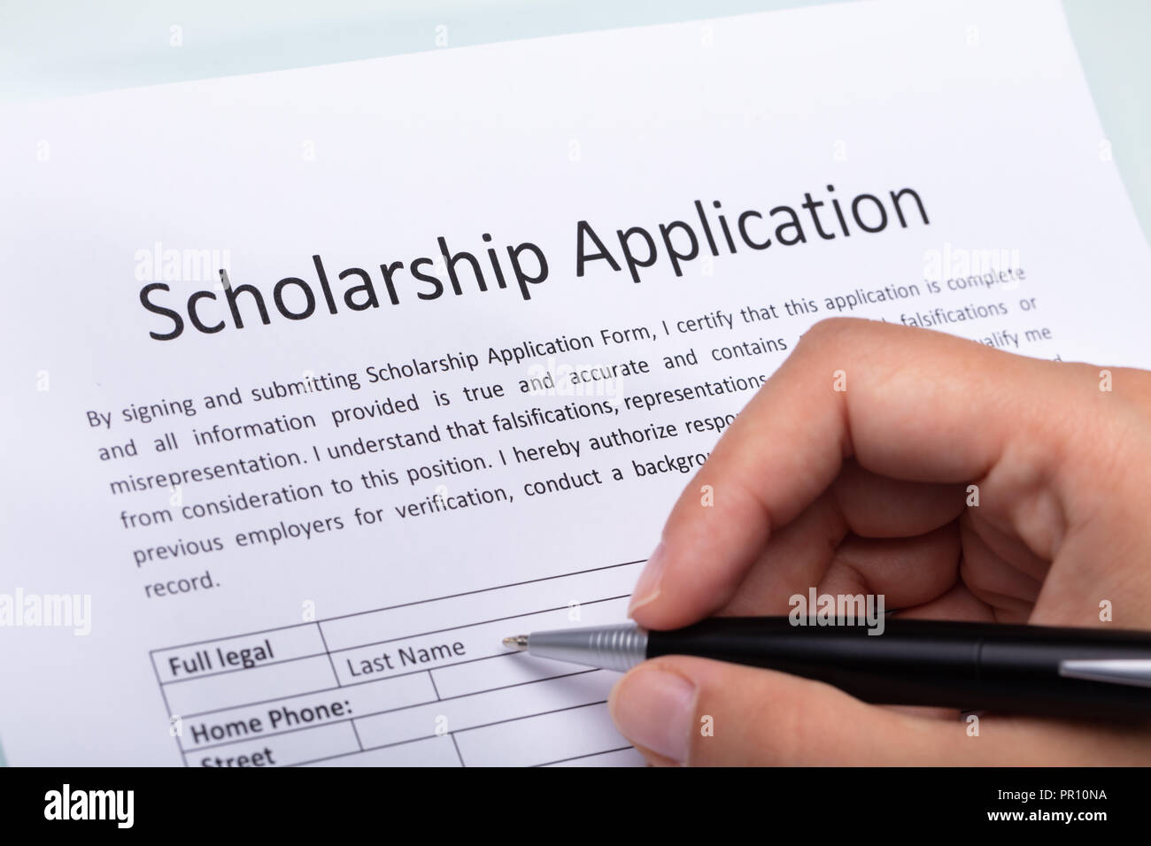 Close-up Of A Person's Hand Filling Scholarship Form With Pen - Stock Image