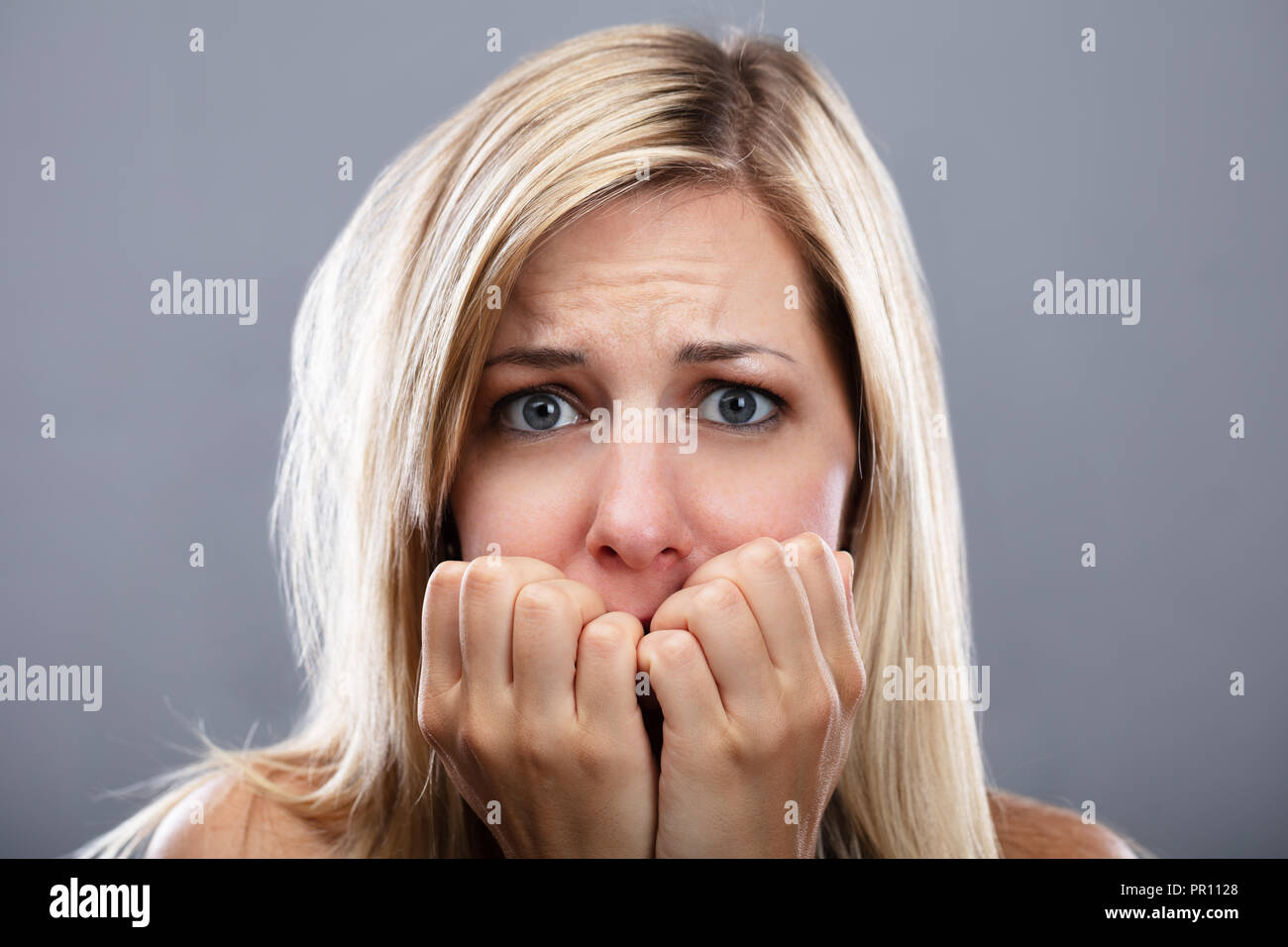 Portrait Of A Scared Young Woman On Grey Background - Stock Image