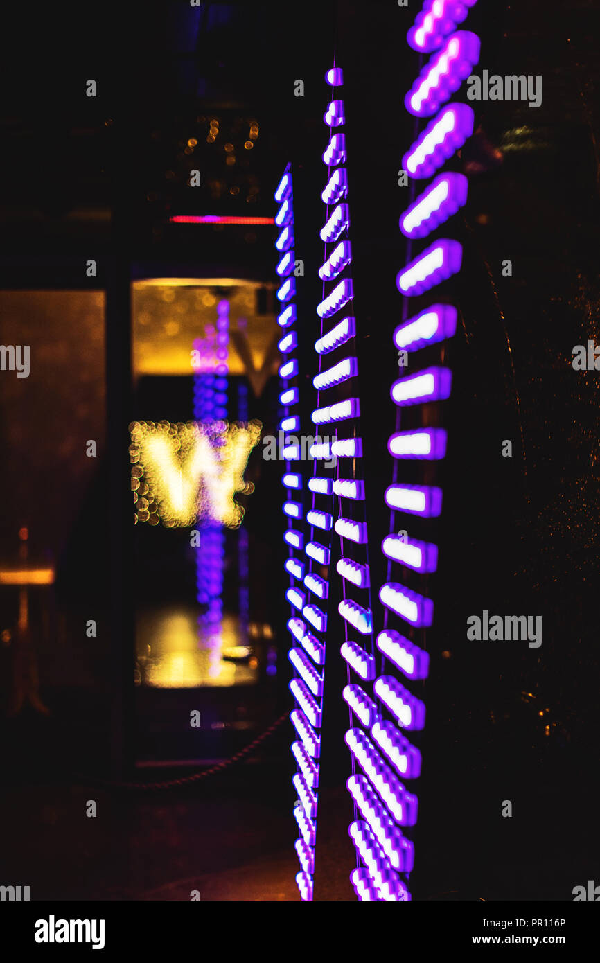 The W logo at the entrance of the W Hotel in Leicester Square at night. London, England. - Stock Image