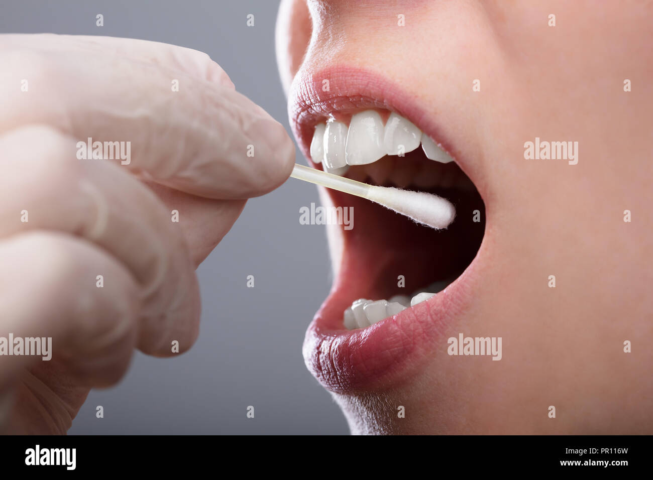 Close-up Of A Woman's Hand Taking Saliva Text From Her Mouth - Stock Image
