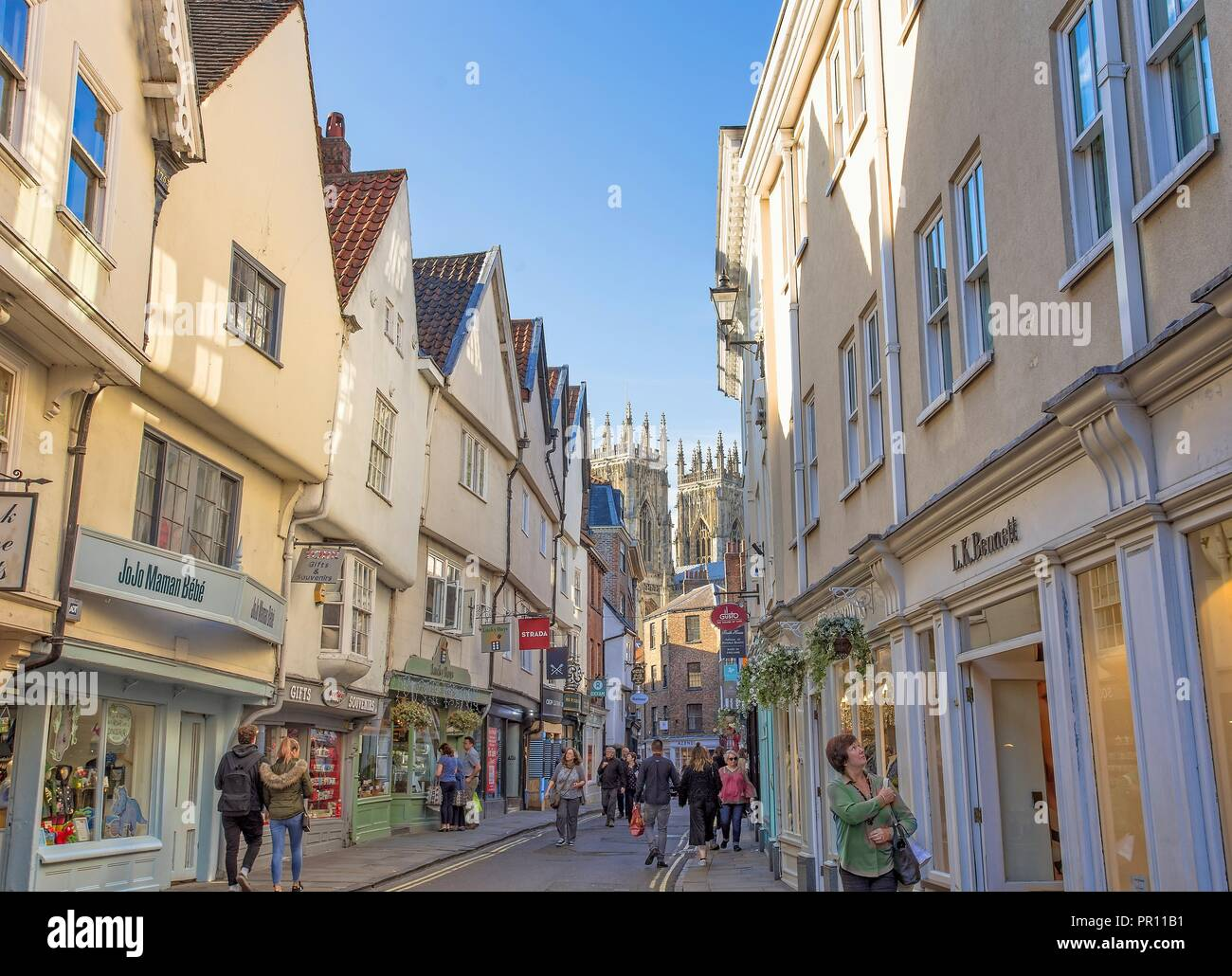 Low Petrergate, a street in York with its shops and the towers of York Minster in the background. Stock Photo