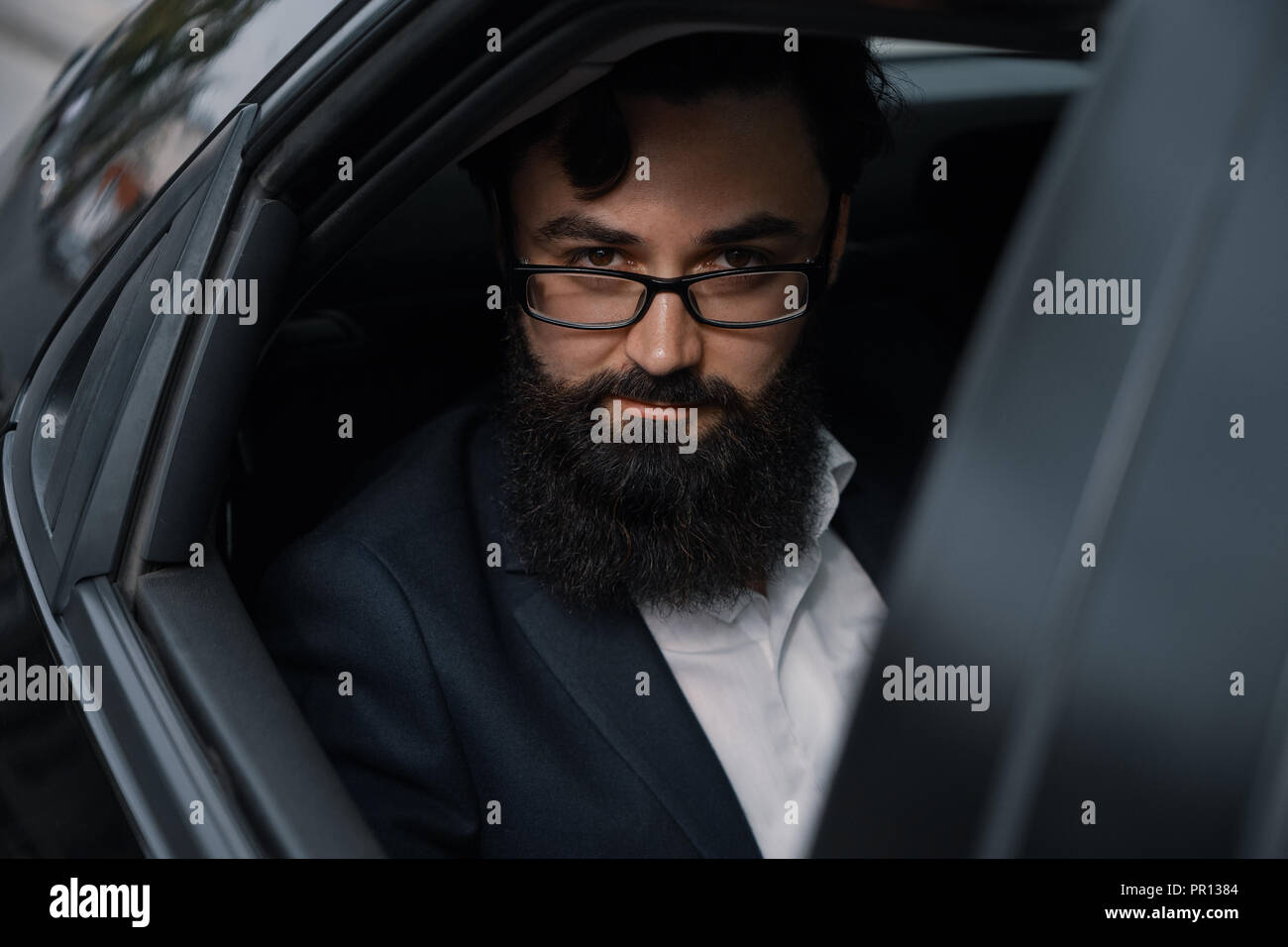 Attractive young businessman in a car looking determined to camera. - Stock Image
