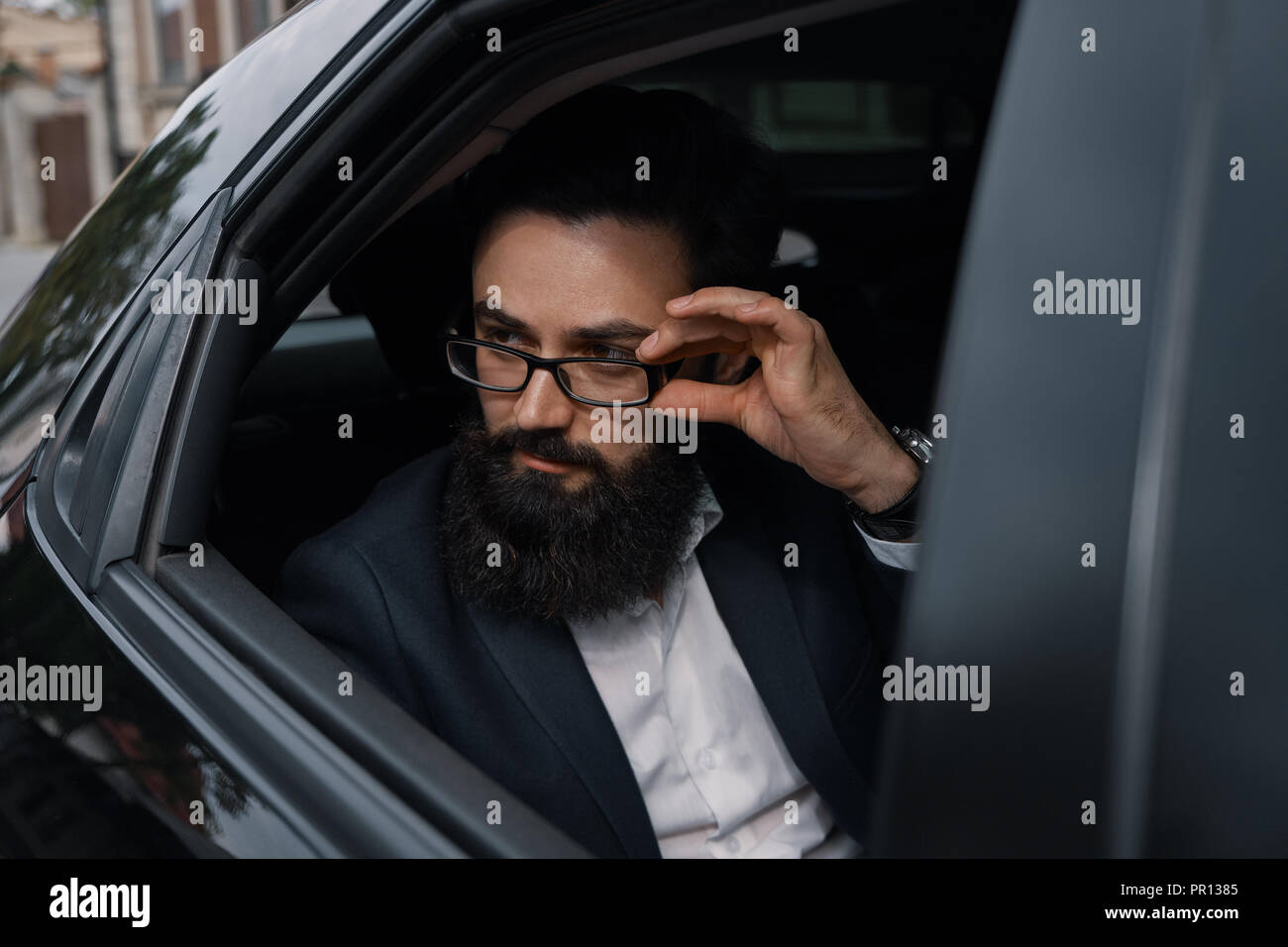 Attractive young businessman in a car looking determined. - Stock Image