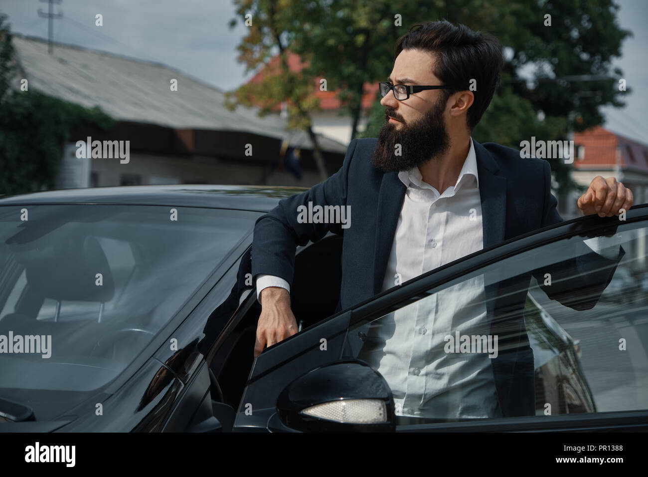Confident in his choice. Confident man in formal wear holding hand on opened car door and looking to the right while fixing his glasses with hand. - Stock Image
