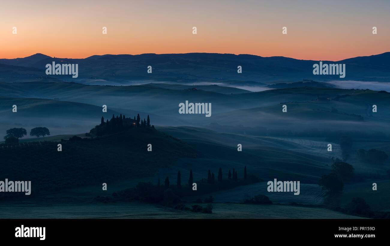 Pre-dawn mist lies in the fields and hills of the Val d'Orcia beyond a farmhouse perched on top of a small outcrop, UNESCO, Tuscany, Italy - Stock Image
