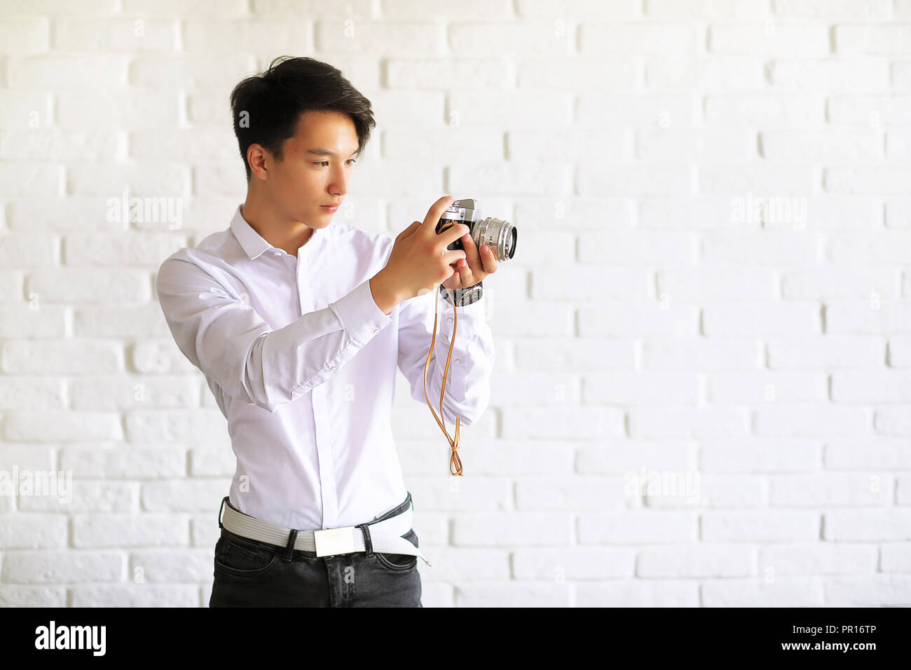 Asian young man with a camera - Stock Image