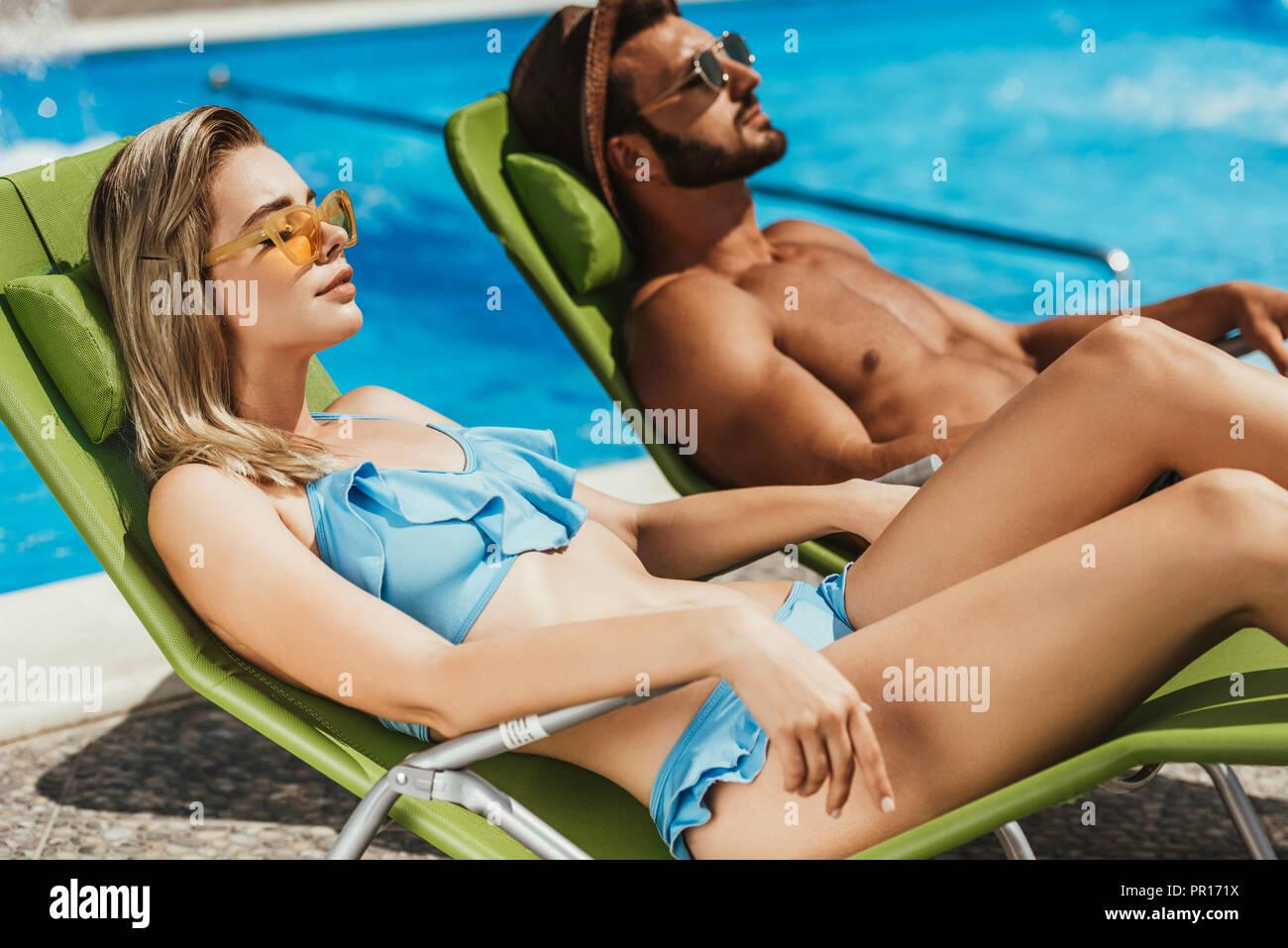 beautiful young couple sunbathing on sunbeds at poolside - Stock Image