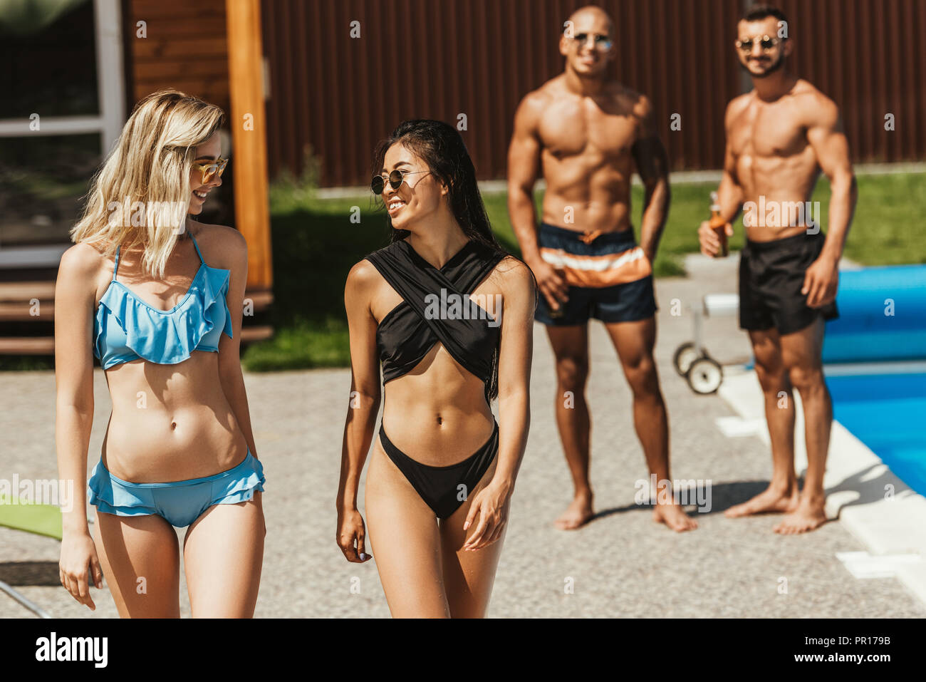 multiethnic beautiful girls in swimsuits and sunglasses walking at poolside with boyfriends behind - Stock Image