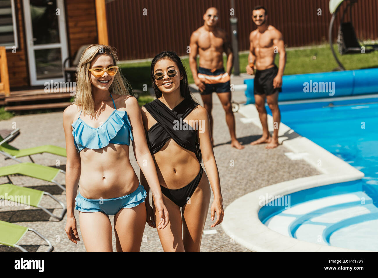 beautiful multicultural girls in swimsuits walking at poolside with boyfriends behind - Stock Image