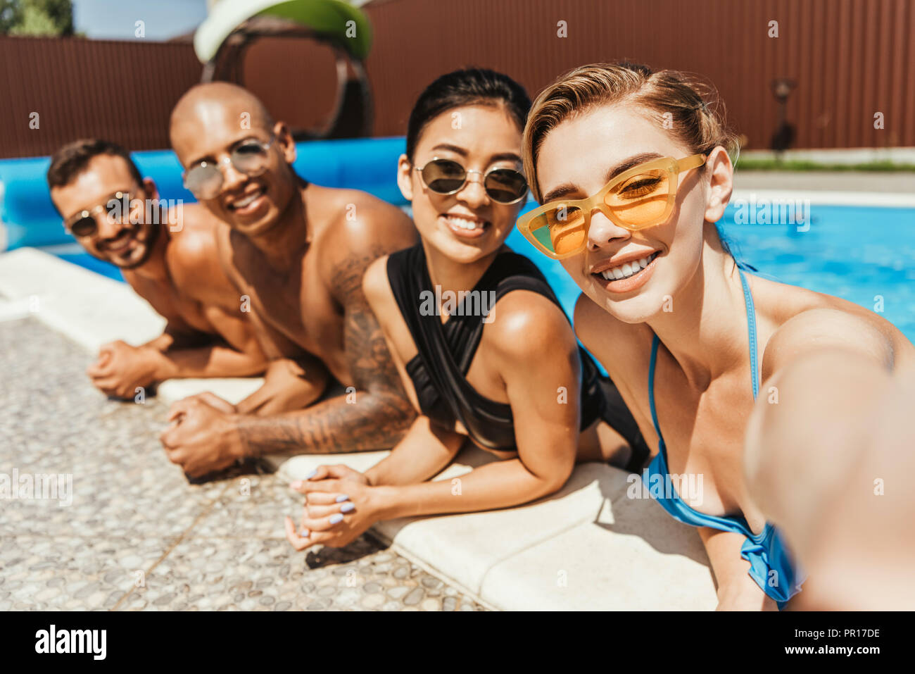 d0b03d9b85 young smiling multicultural people in swimsuits and sunglasses posing in  swimming pool - Stock Image