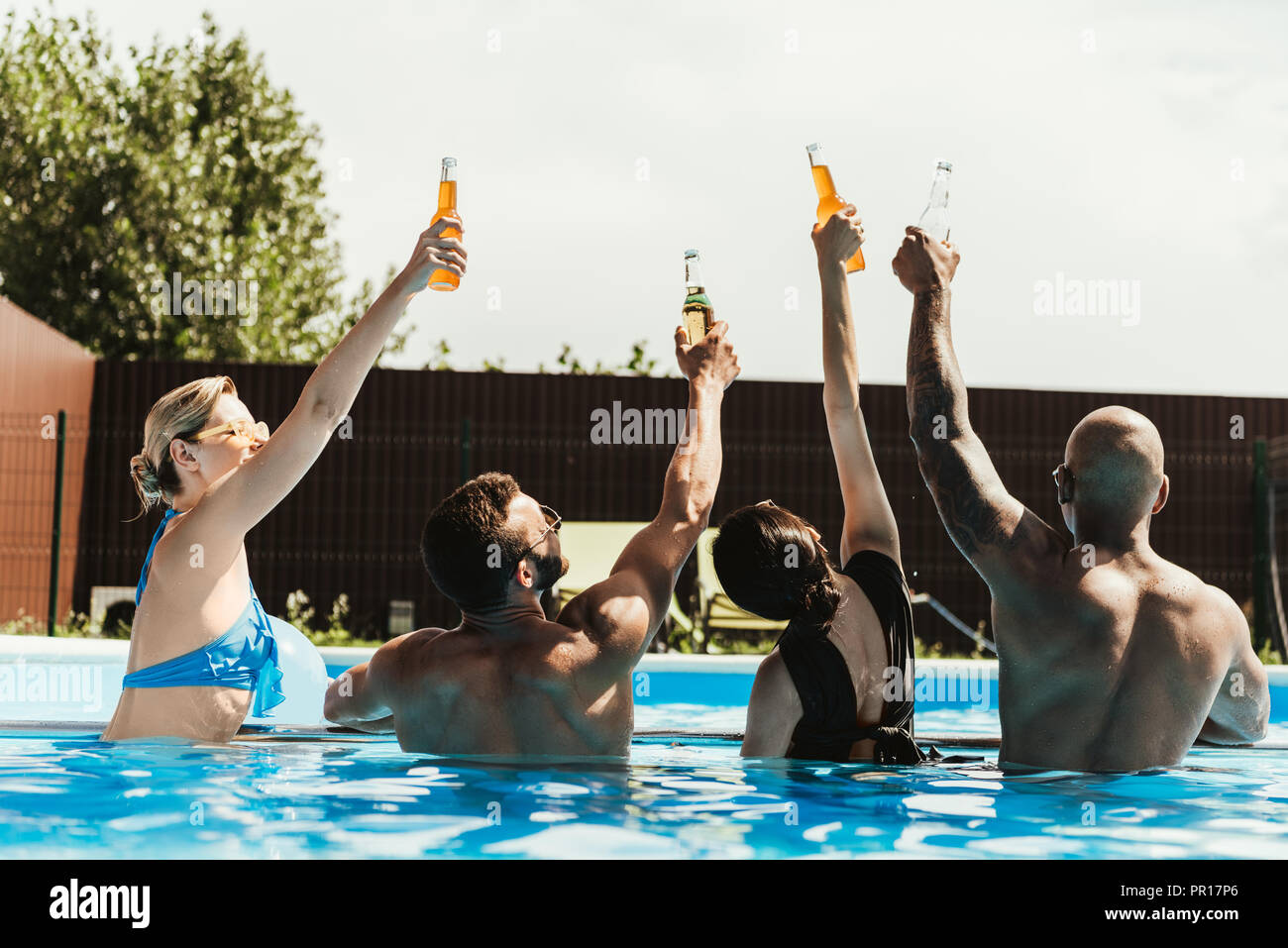 back view of multicultural friends rising up bottles of beer in swimming pool - Stock Image