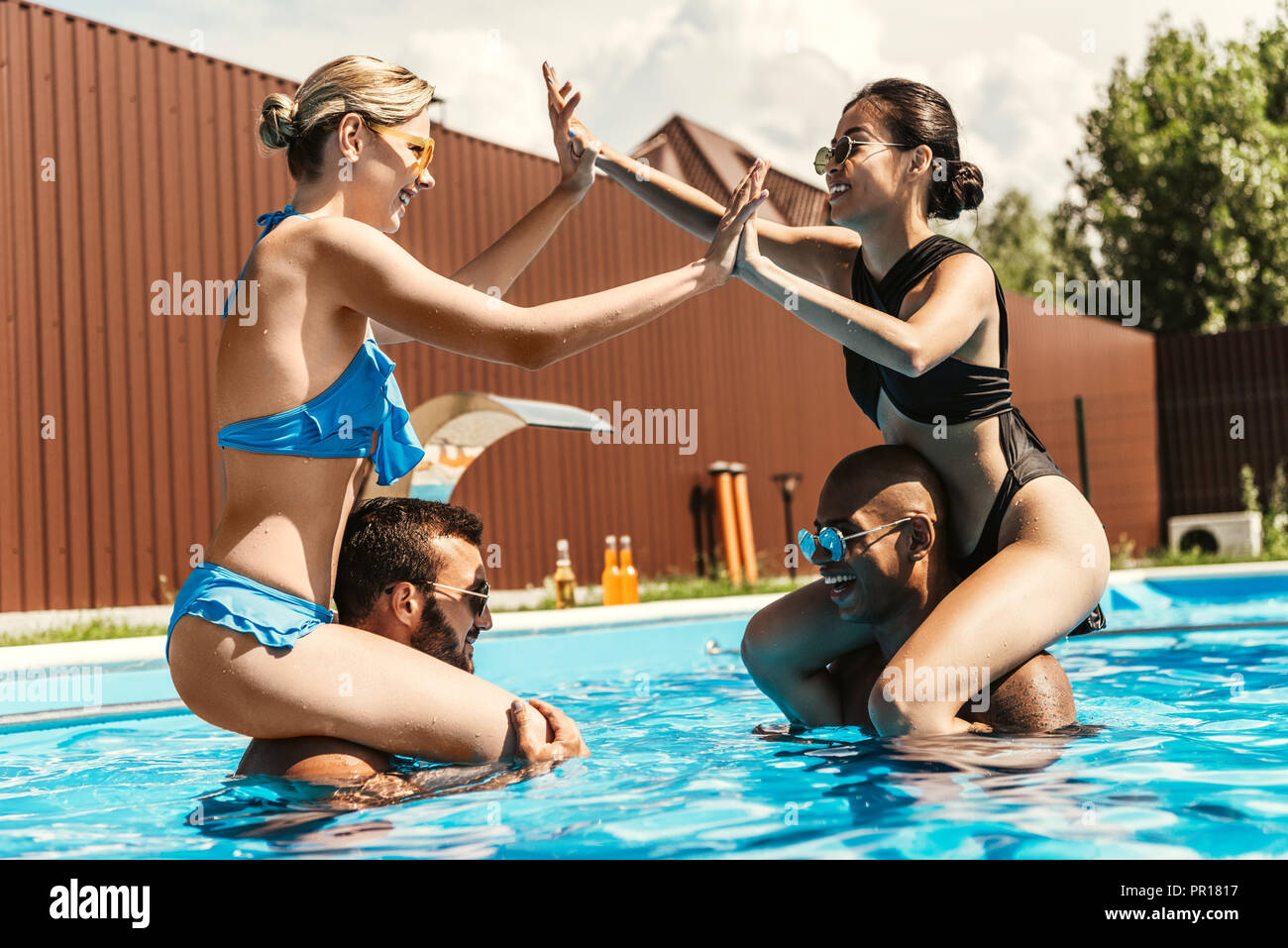 multiethnic girlfriends playing and sitting on shoulders of boyfriends in swimming pool - Stock Image