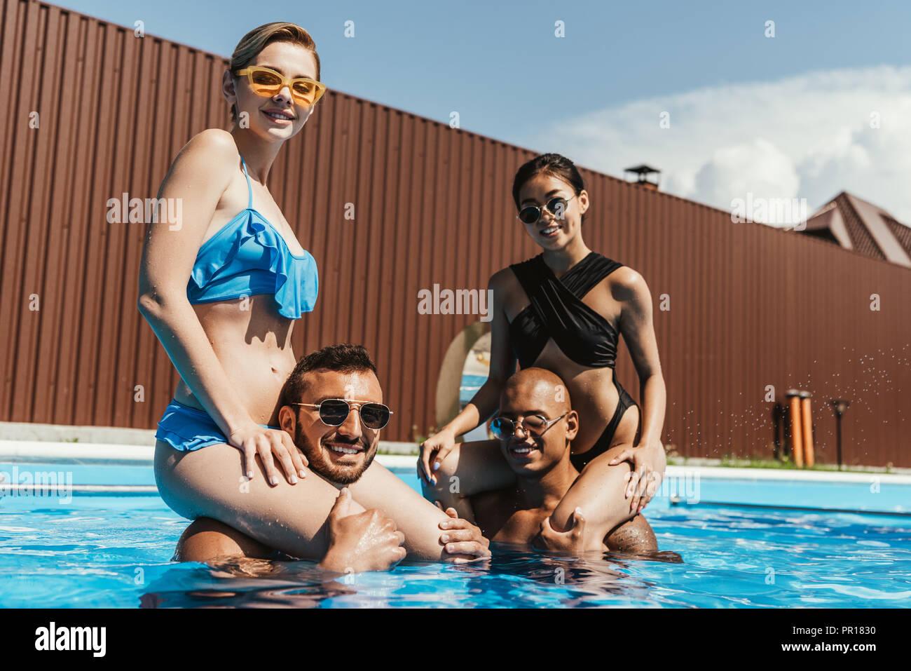 multiethnic girls sitting on shoulders of boyfriends in swimming pool - Stock Image
