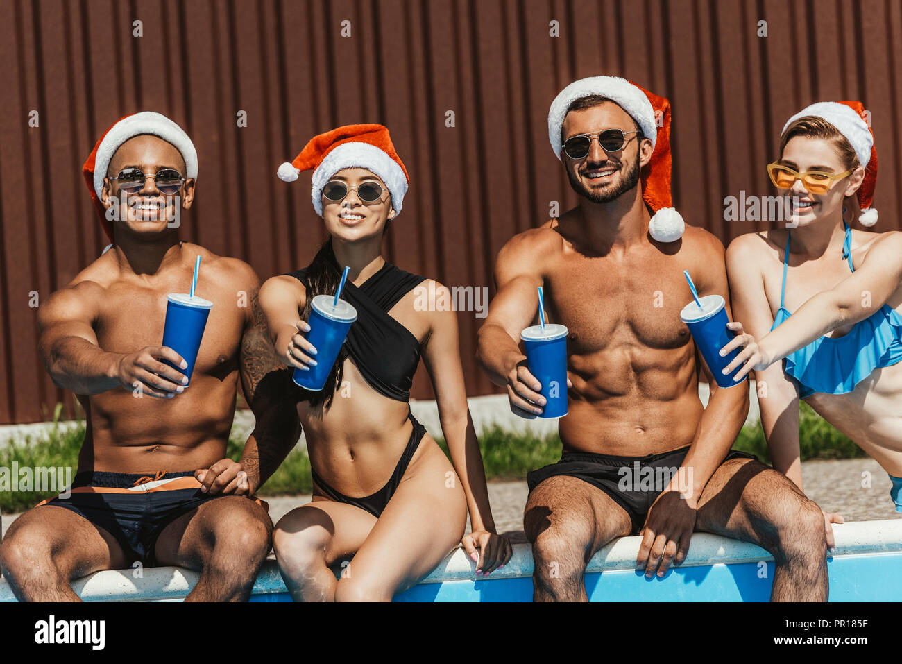 smiling multicultural friends in santa hats with drinks - Stock Image