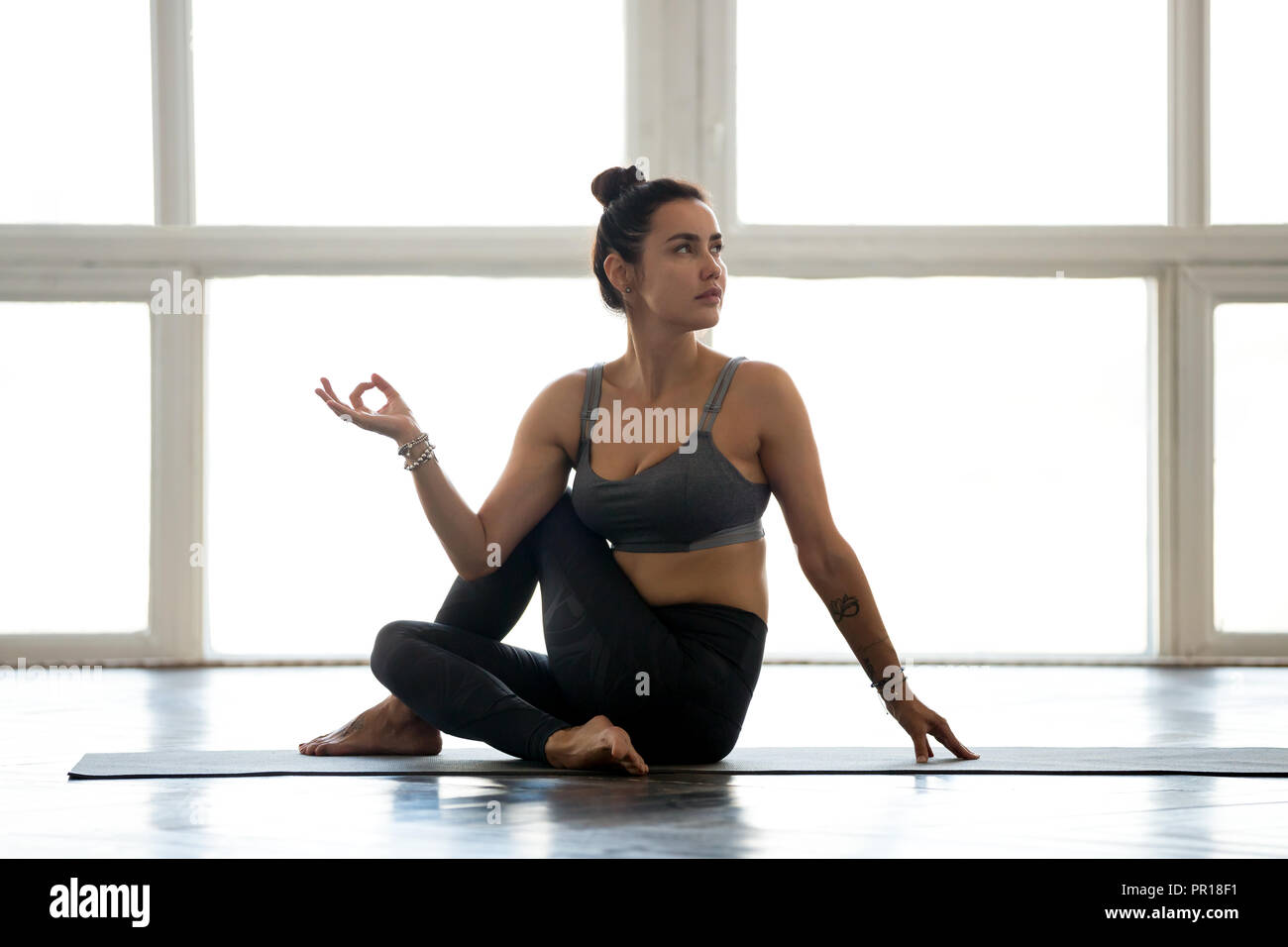 Young sporty attractive woman practicing yoga, doing Revolved Ea - Stock Image