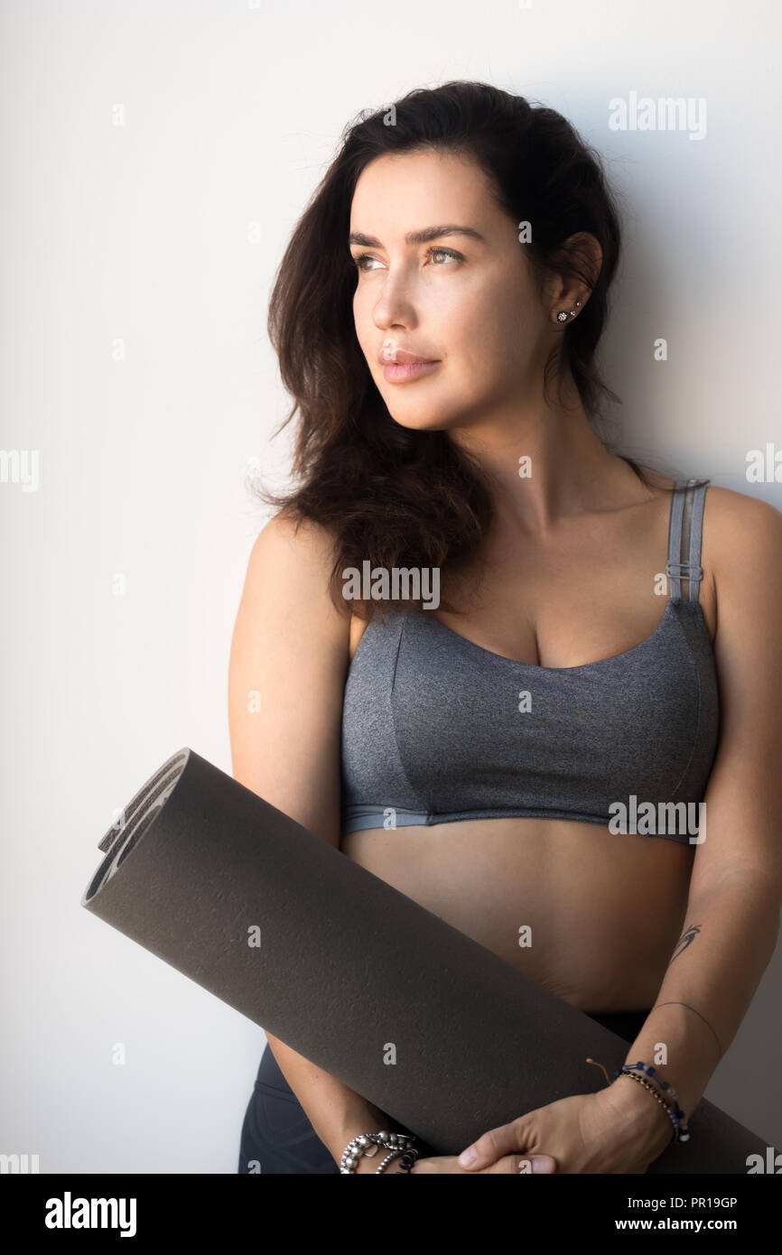 Young yogi attractive woman holding yoga or fitness mat Stock Photo