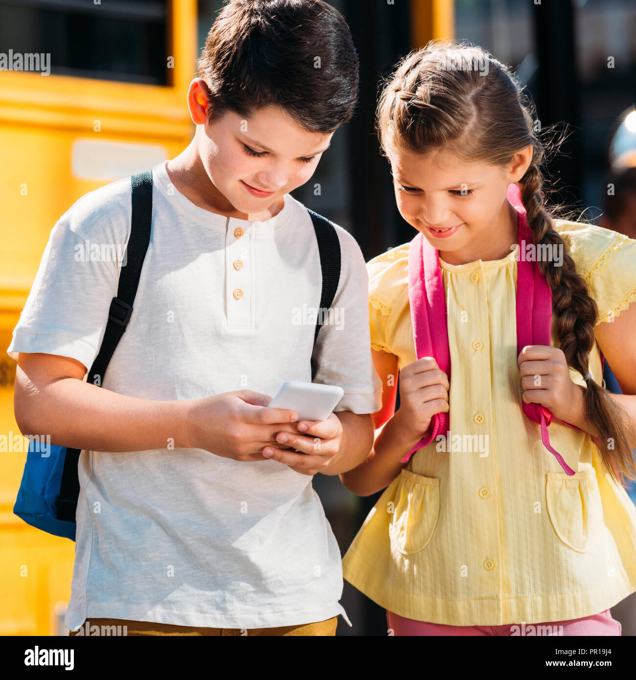 happy little scholars using smartphone together in front of school bus - Stock Image