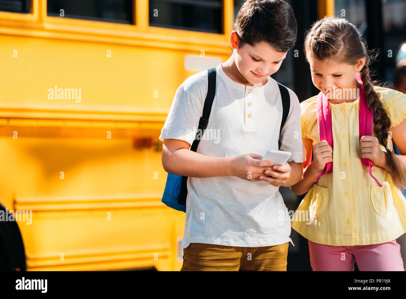 adorable little scholars using smartphone together in front of school bus - Stock Image