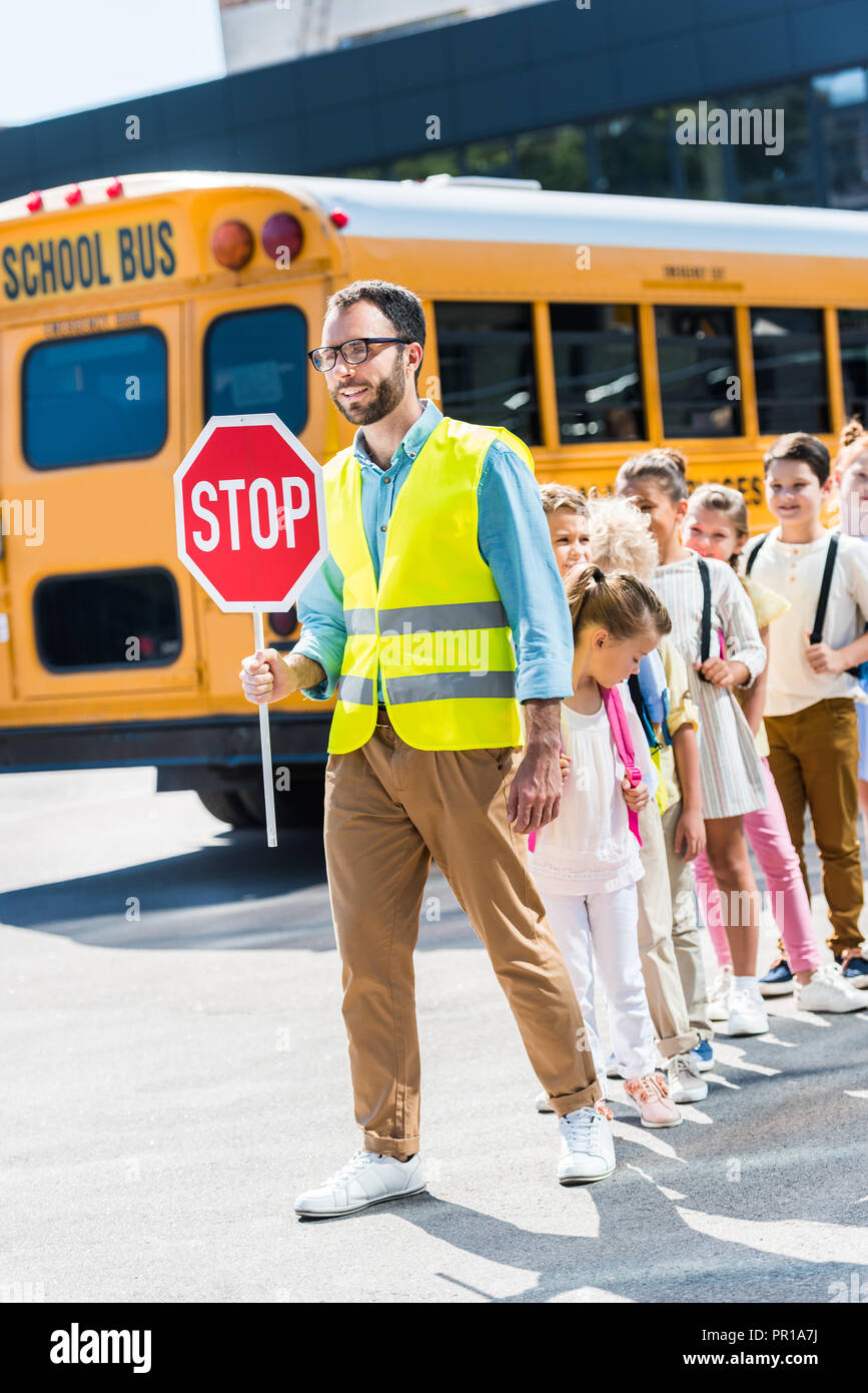 traffic guard crossing road with happy pupils in front of school ...