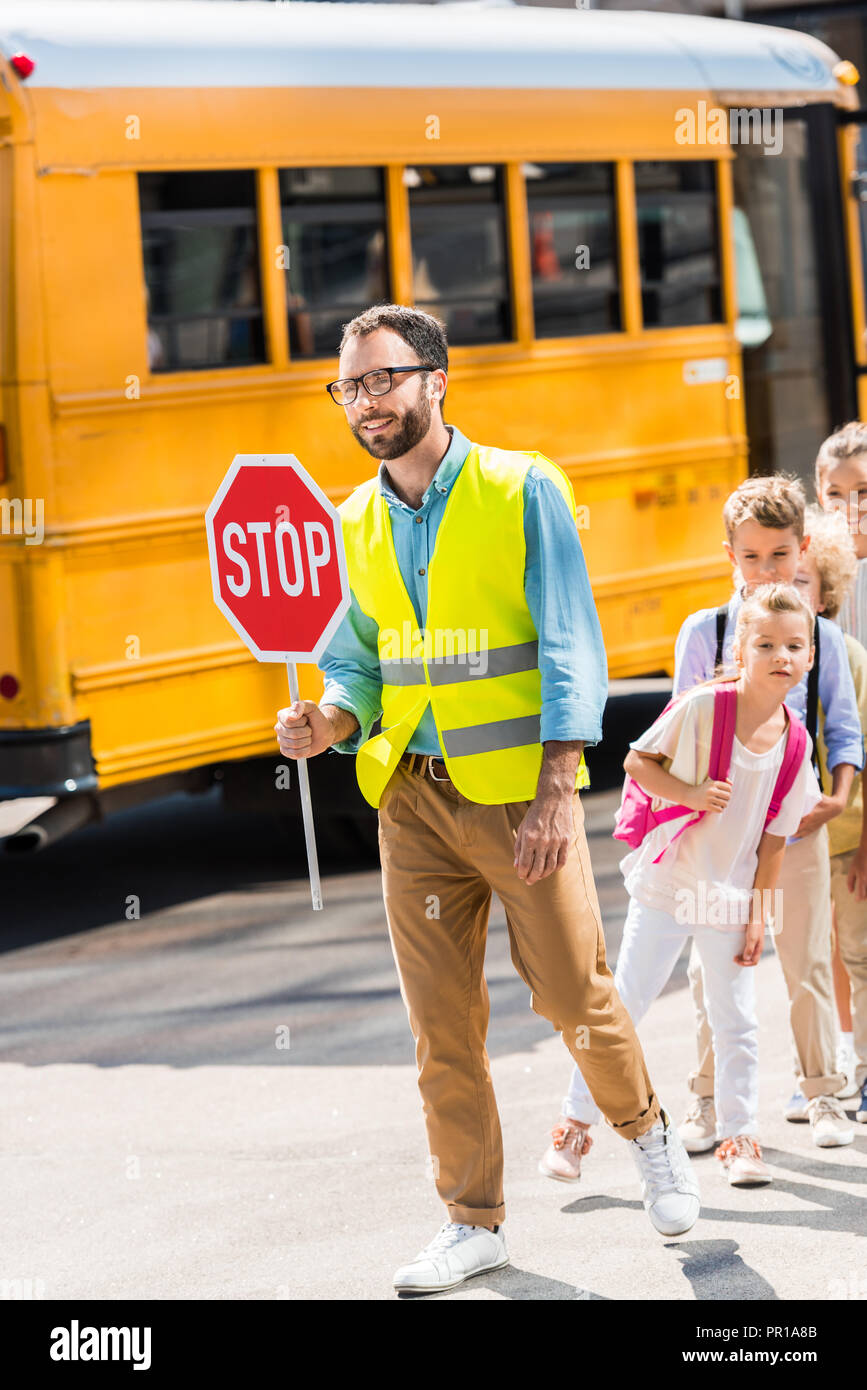 happy traffic guard crossing road with pupils in front of school ...