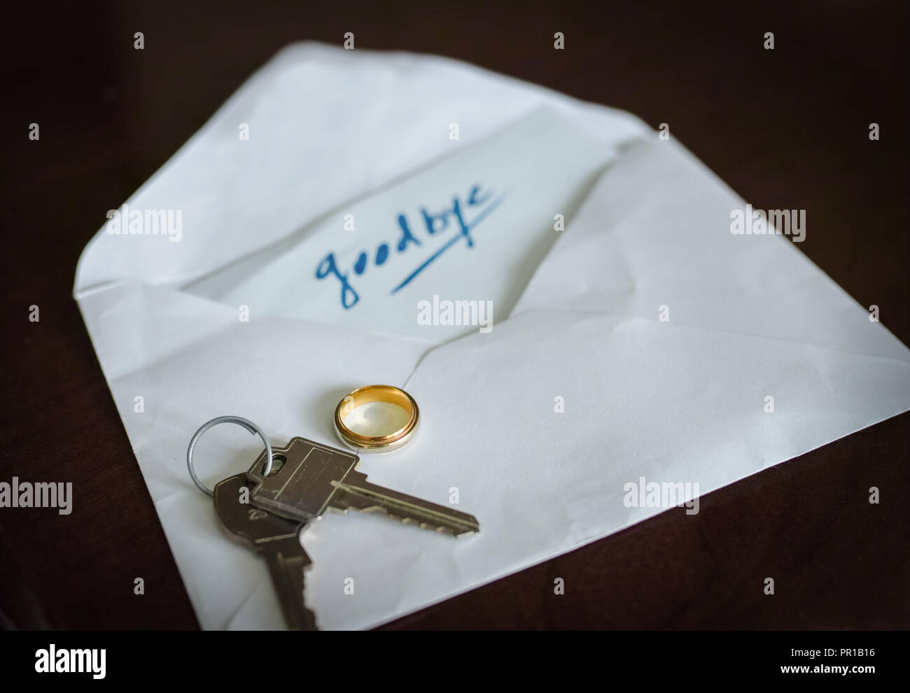 On the table, she or he, left the keys, the wedding ring and a enveloppe with this word inside: Goodbye - Stock Image
