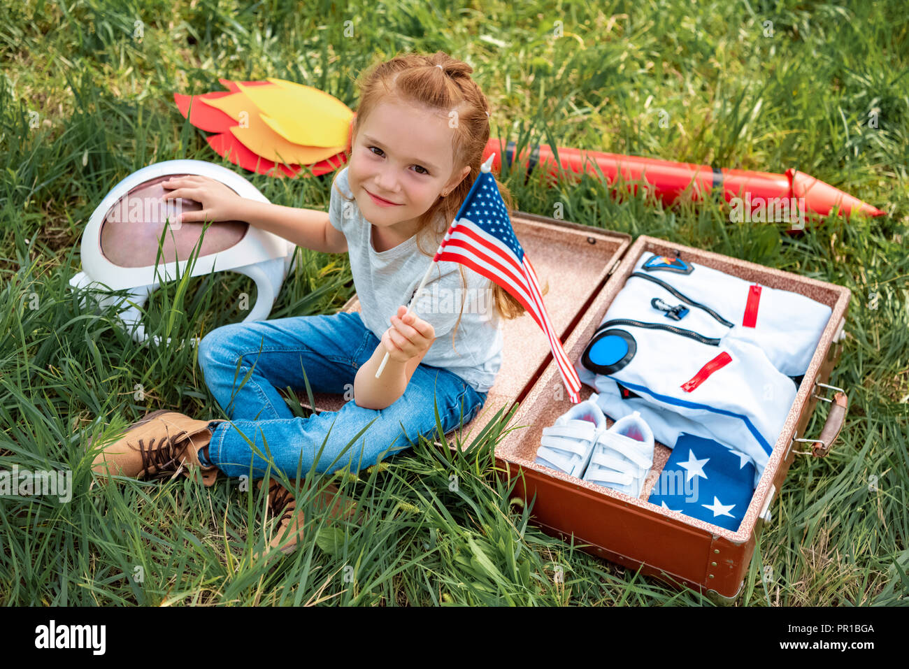 smiling kid with american flagpole in hand sitting near suitcase with astronaut costume and rocket on green grass - Stock Image