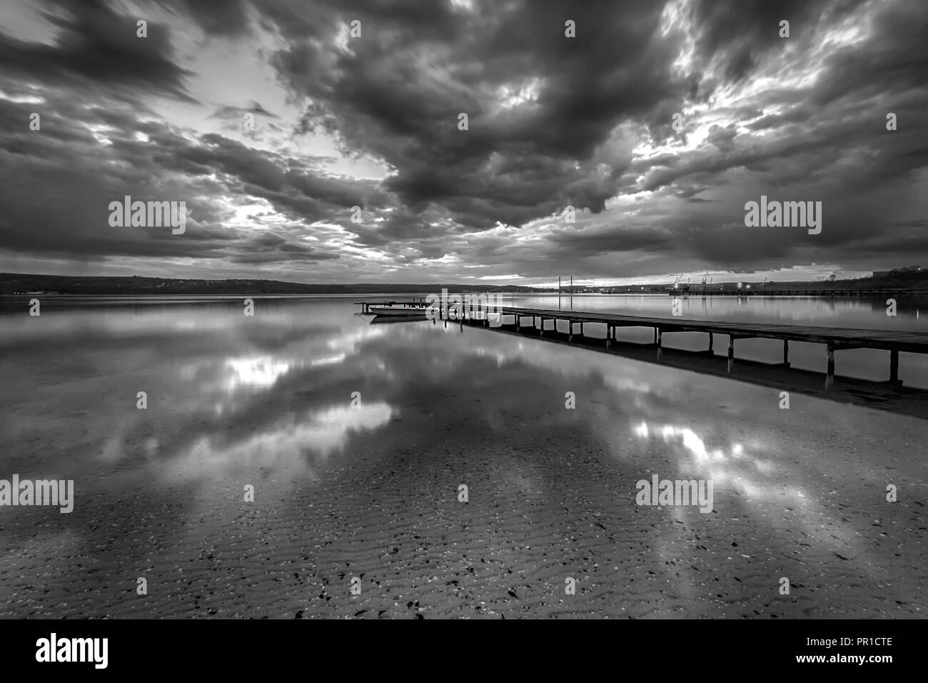 Stunning black and white long exposure seascape with clouds reflection