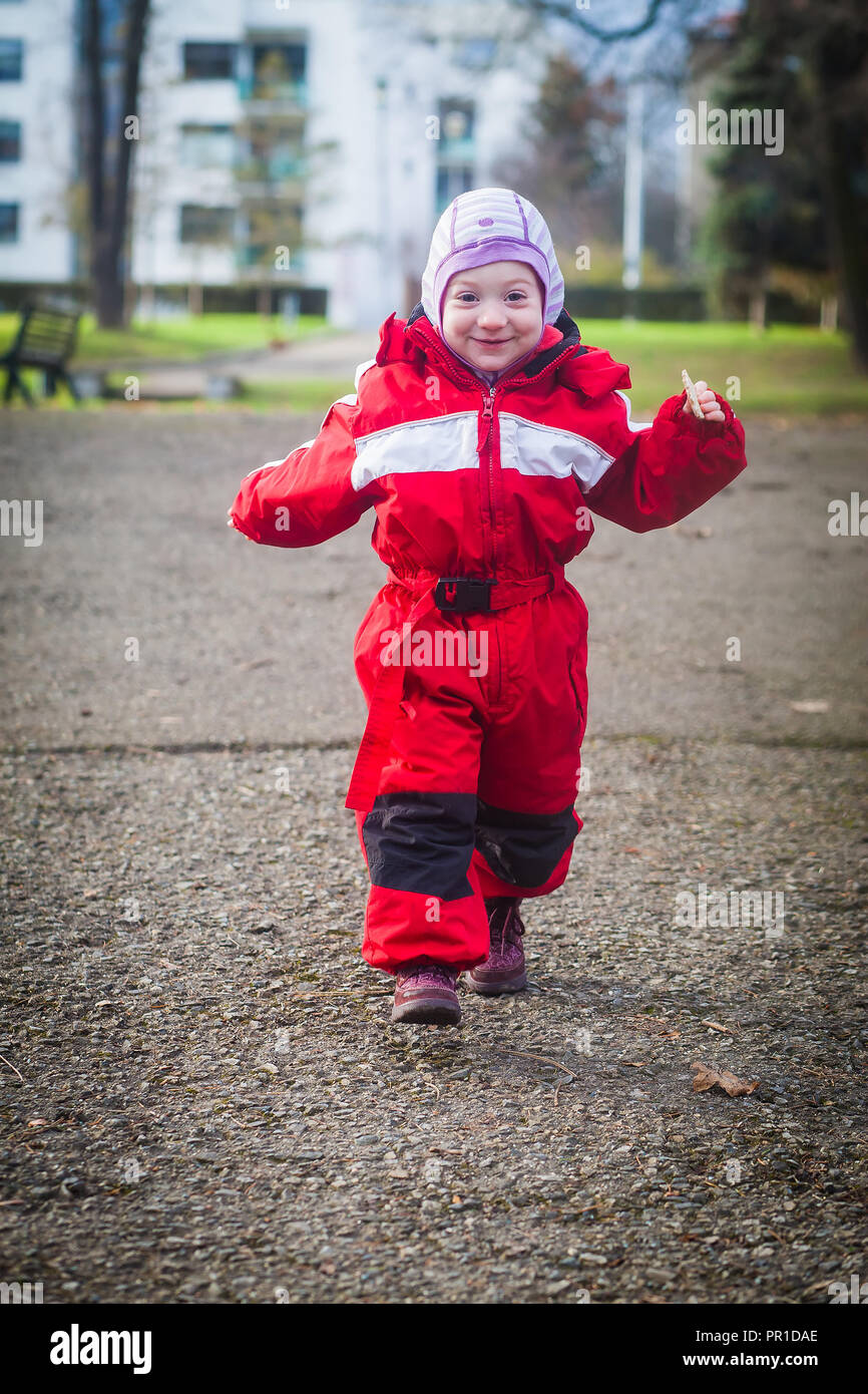 Funny toddler in red winter jumpsuit runs happily towards camera - Stock Image