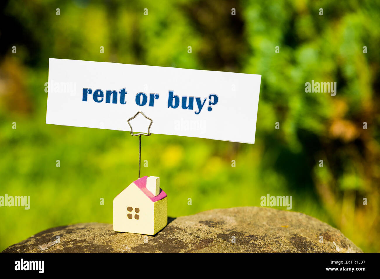 choosing rent or buy option ,small house model isolated on nature background, housing real estate and property owner concept. real estate question, businessman making decision.Country house. Copy space - Stock Image