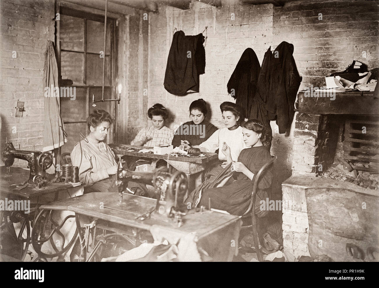 Five young seamstresses working for a starvation wage in a New York tenement sweat shop.  Circa 1906.  After a photograph by Lewis Hine, 1874-1940.  Hine was a sociology teacher who used photography to record social problems and spur reform. - Stock Image