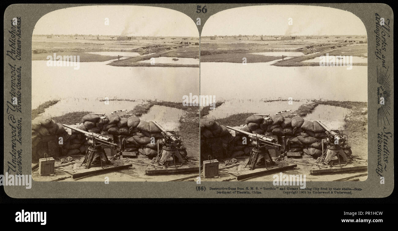 Destructive guns from H.M.S. 'Terrible' and distant burning city fired by their shells, Ricalton, James, Underwood and Underwood - Stock Image