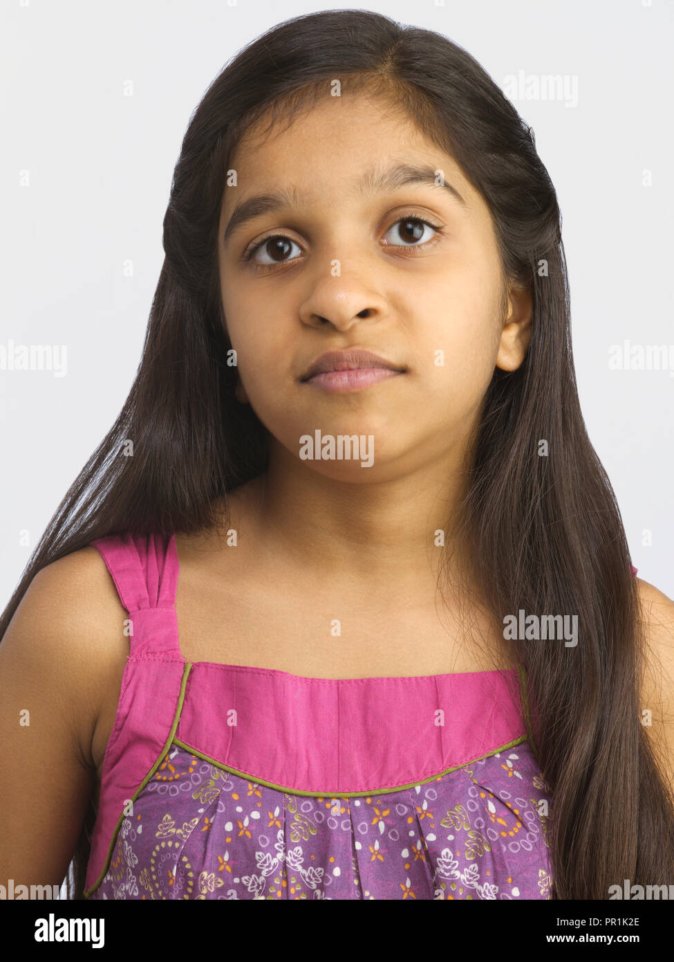 YOUNG GIRL FROWNING SHOT AGAINST A PLAIN BACKGROUND Stock Photo