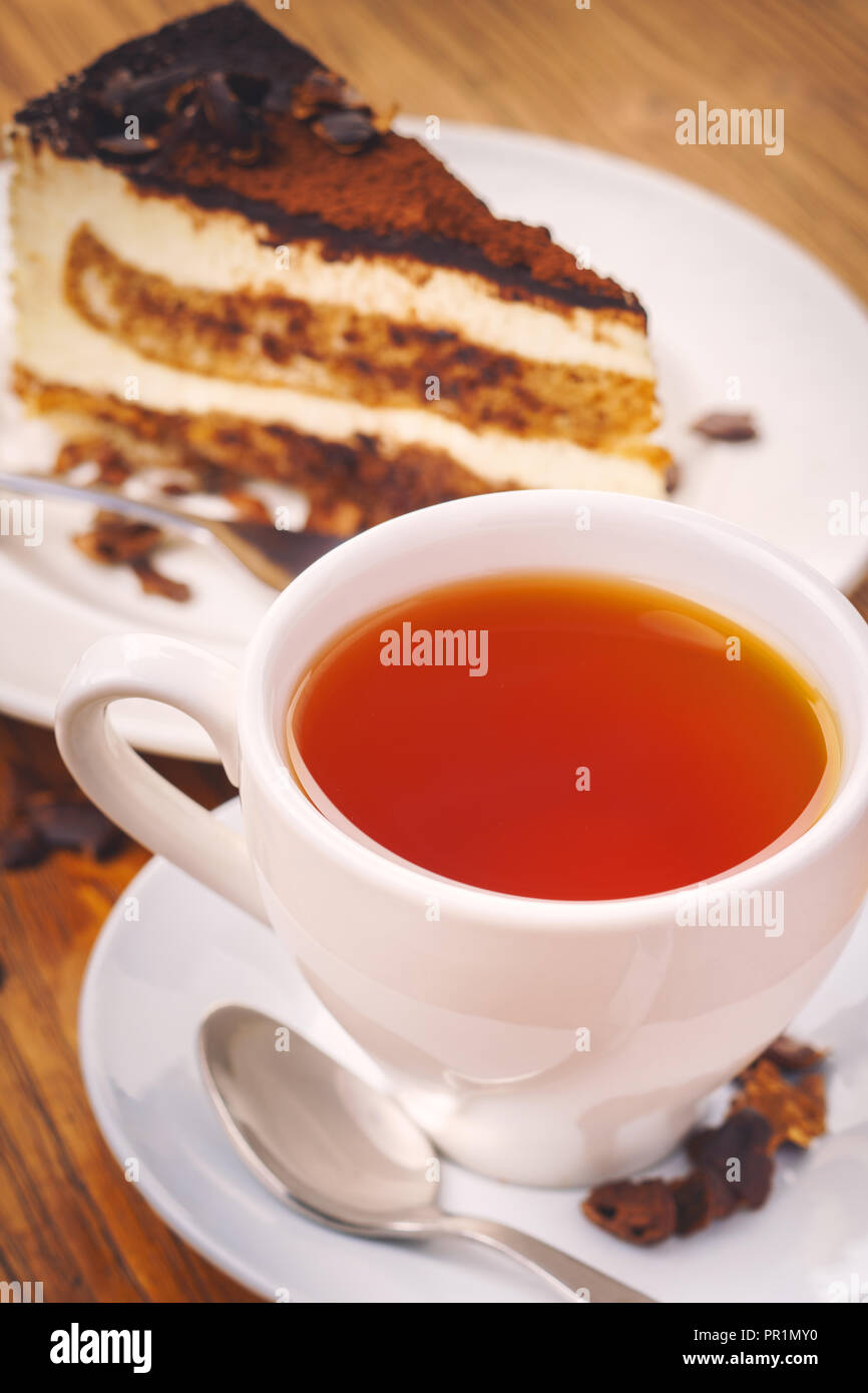 Cup of fresh hot tea with delicious piece of chocolate cake on the wooden table - Stock Image