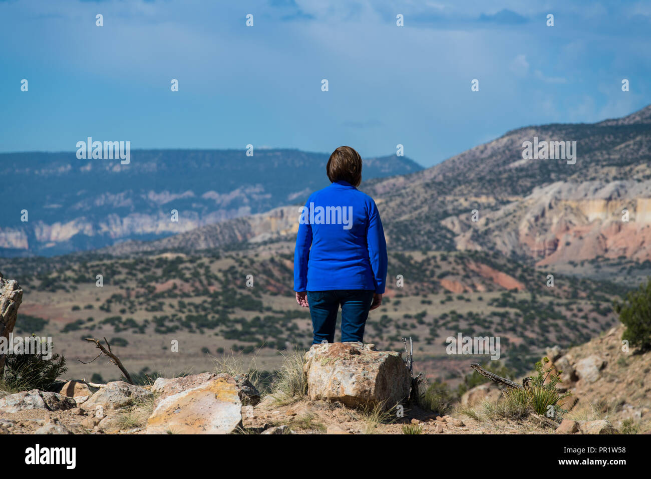 Woman wearing a blue fleece pullover looking out over a vast colorful landscape and stormy clouds in the American Southwest - Stock Image