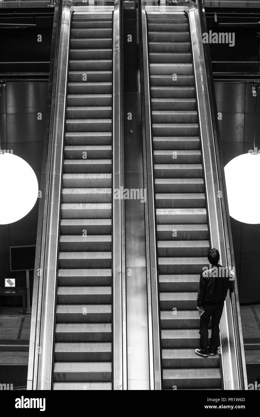 Man rising on moving stairways - Stock Image