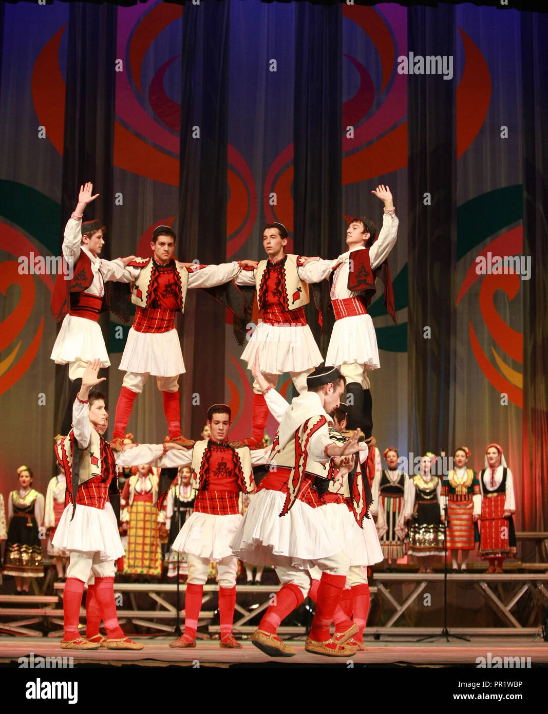 People in traditional folklore costumes perform folk dance bulgarian horo on National folklore fair in the Sofia, Stock Photo