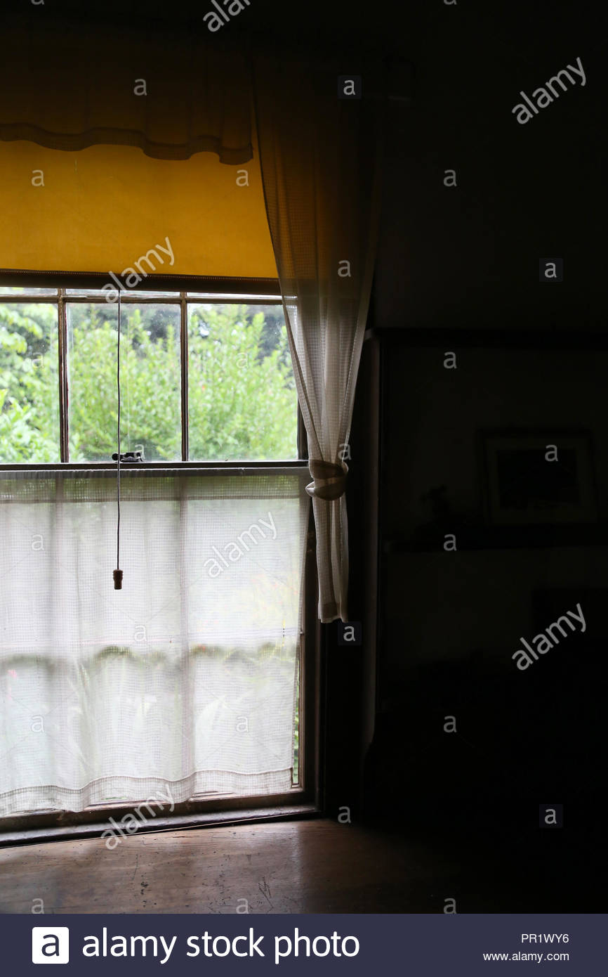 View through a homey curtained window. - Stock Image