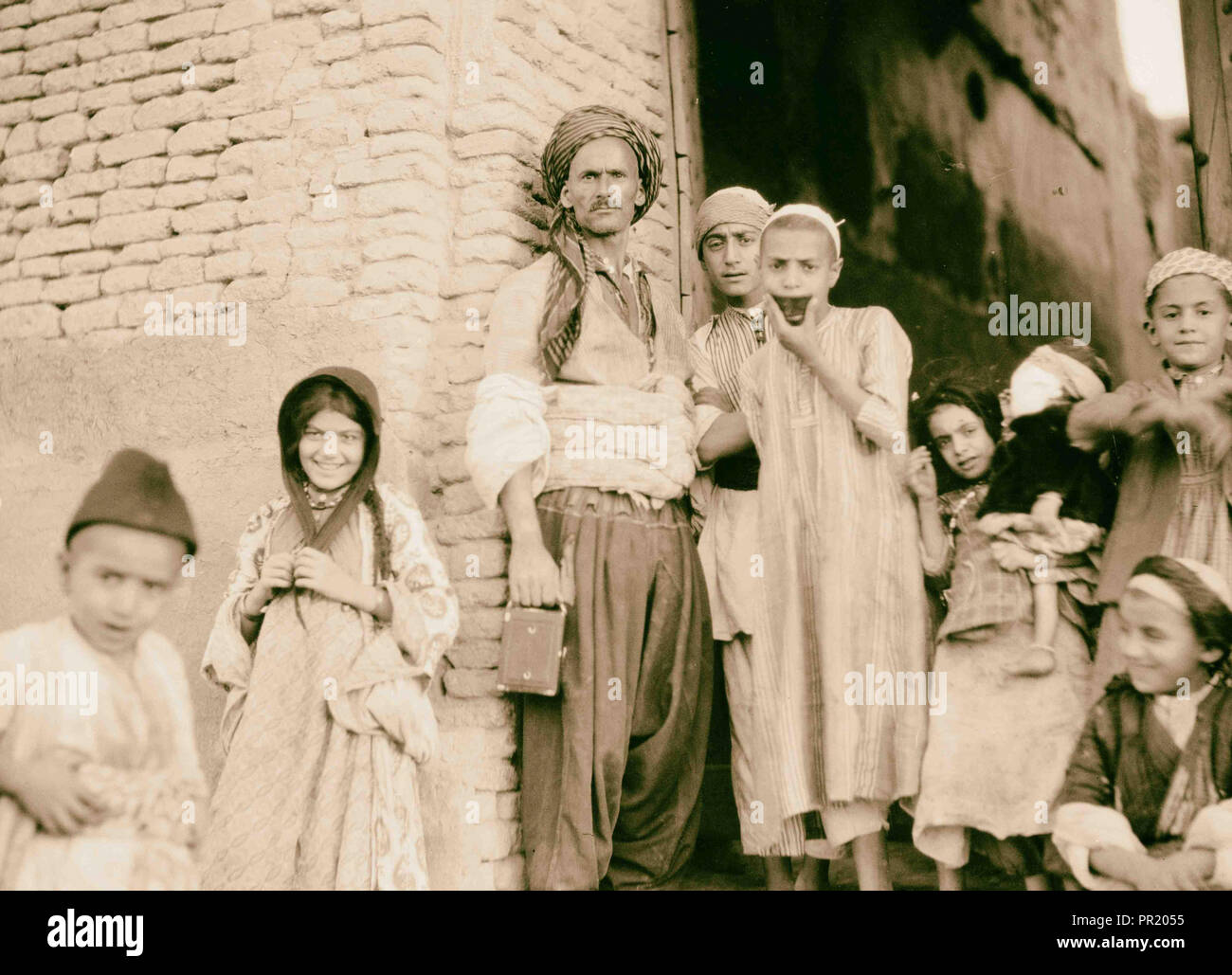 Iraq. Arbela. (Erbil). Center of Ishtar cult in Assyrian period, 2200 B.C. Typical group man, boys, and girl. 1932, Iraq, Irbīl - Stock Image