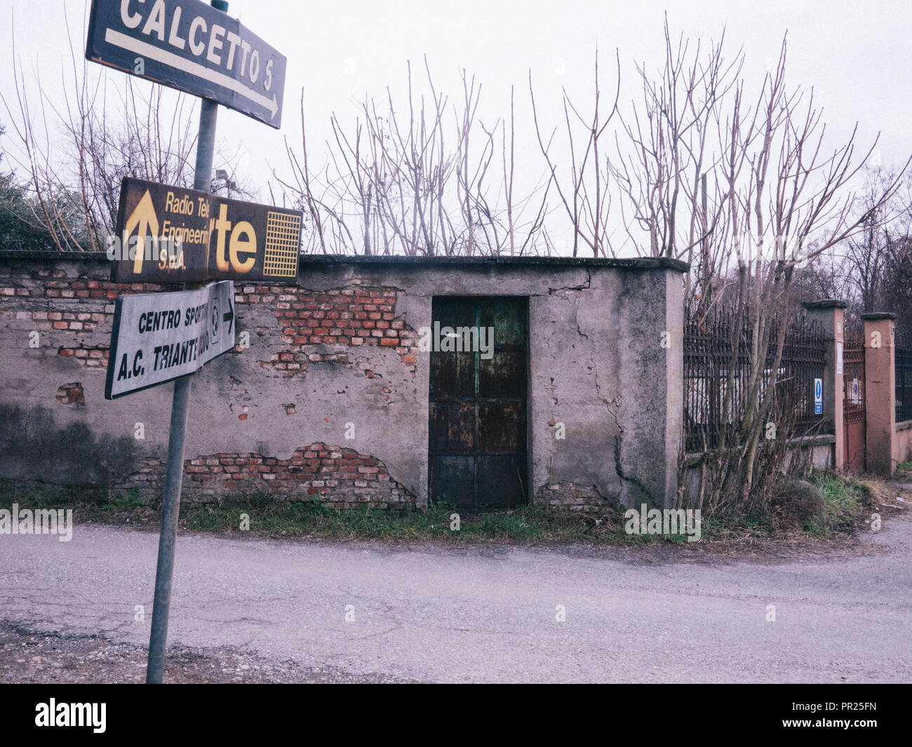 A dull-looking crossroad with old worn-out street signs. Looks very abandoned to itself and sad. Almost post apocalyptic. Wall fence and gate - Stock Image