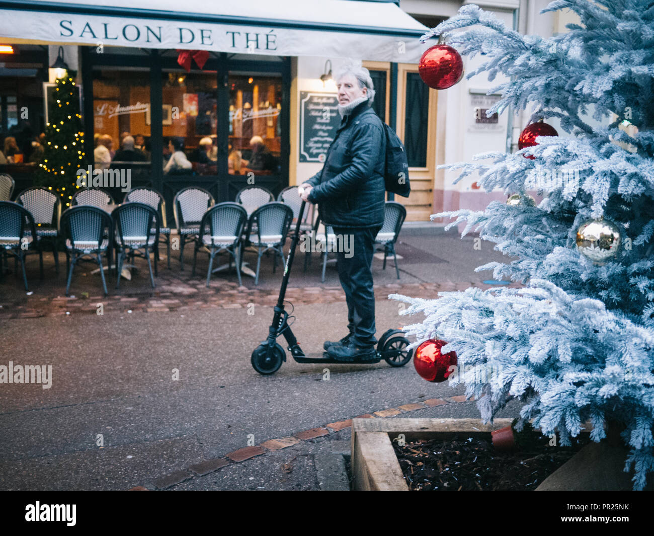A man goes in his scooter at Christmas near a bar which sells tea with some chairs outside. There's a Christmas tree with balls in the foreground - Stock Image